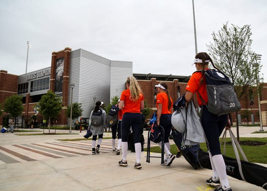 Members of the Auburn softball team walk toward Davis Diamond in College Station, Texas.