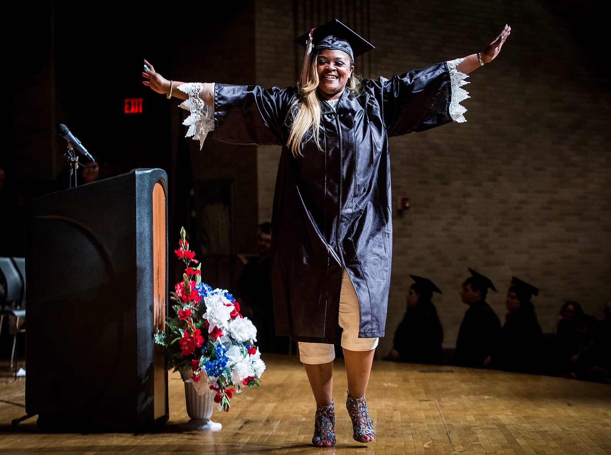 Angela Bennett celebrates while walking the stage to receive her high school diploma during the 2019 MCS Adult Education Program graduation ceremony at Central Thursday night.