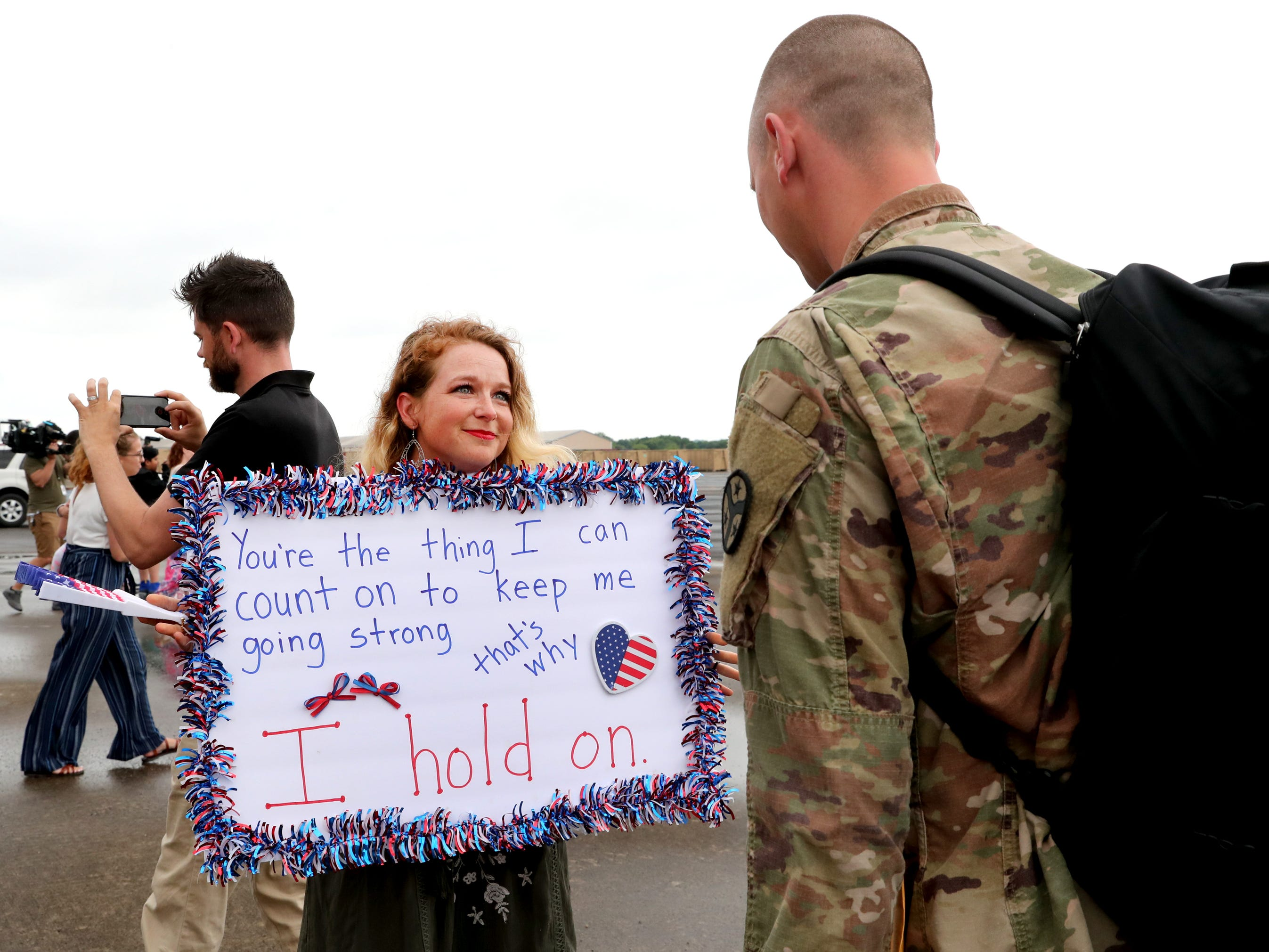 Kristy Bobo shows her homemade sign to her husband Derek Bobo, with the 278th ACR after he gets off the plane at the Volunteer Training Site in Smyrna, from a 9 month overseas deployment on Thursday, May 9, 2019.