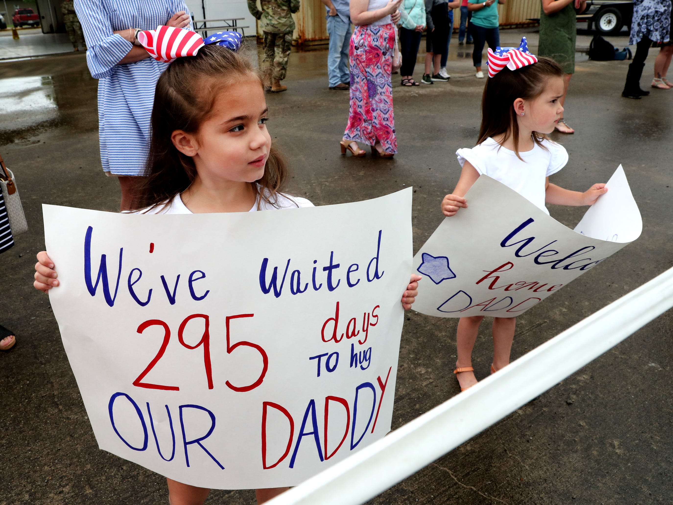Riley Fleming, 6, left and Harper Fleming, 4, both hold up signs as they wait for their dad Staff Sgt. Kyle Fleming with the 278th ACR, to return to the Volunteer Training Site in Smyrna, from a 9 month overseas deployment on Thursday, May 9, 2019.