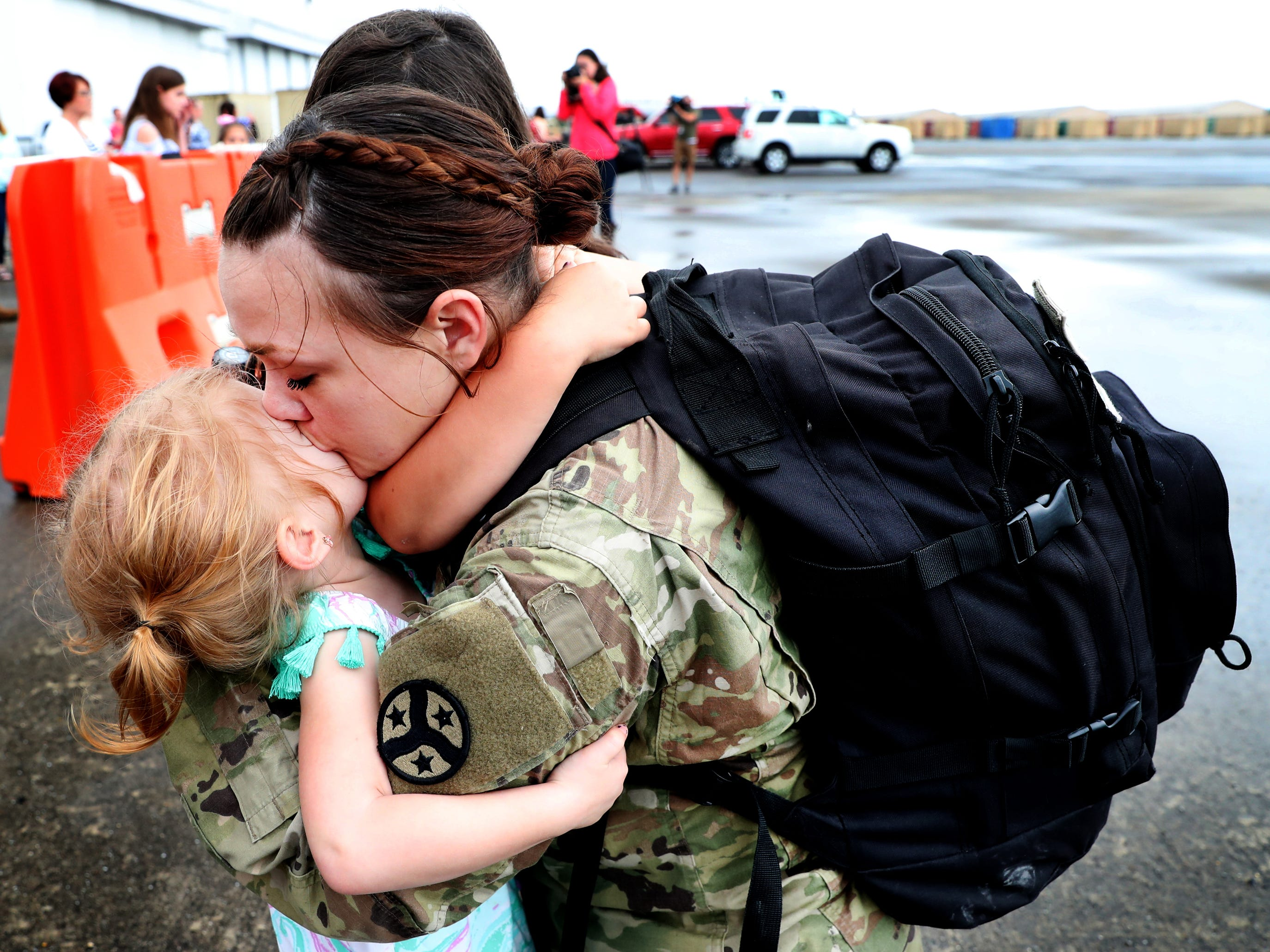 Specialist Katie Byrd, with the 278th ACR kisses her daughter Rosie Byrd, 3, as her other daughter Natalie Byrd, 6 hugs her neck after she gets off the plane at the Volunteer Training Site in Smyrna, from a 9 month overseas deployment on Thursday, May 9, 2019.