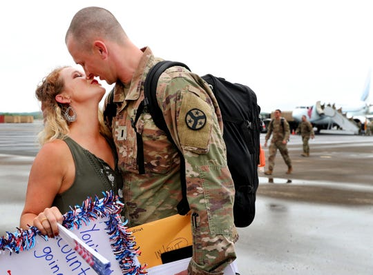 Kristy Bobo kisses her husband Derek Bobo after he gets off the plane after a nine-month overseas deployment.