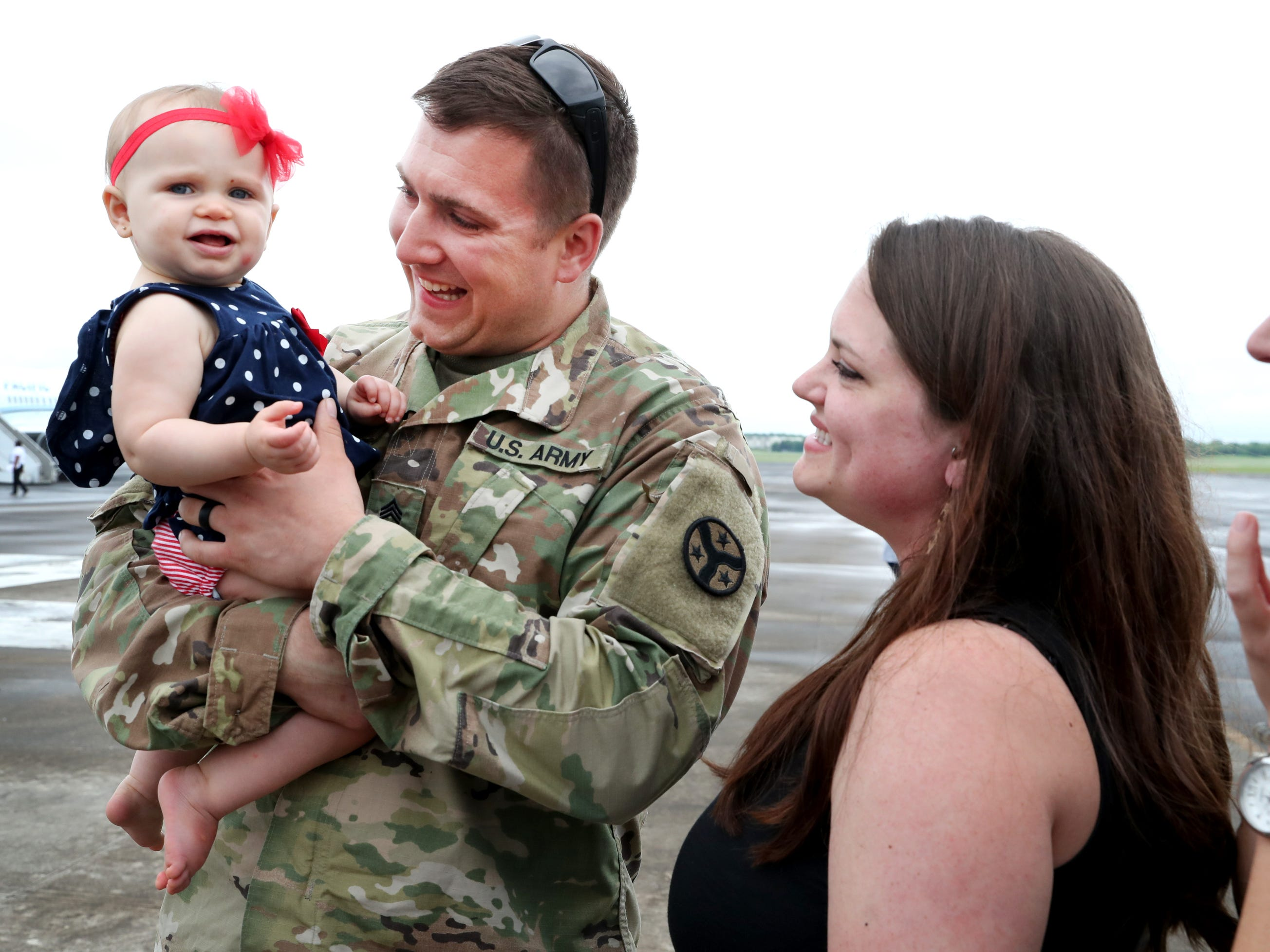 Molly Baker watches as her husband Sgt. Jake Baker with the 278th ACR, holds their 1 year-old daughter Emelyn Baker after he got off a plane, at the Volunteer Training Site in Smyrna, from a 9 month overseas deployment on Thursday, May 9, 2019.
