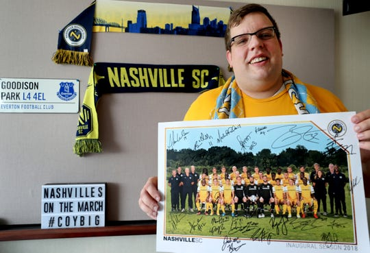 Clay Trainum, an external relations specialist at MTSU, is one of the Nashville SC's biggest fans. Trainum is also part of The Roadies, Nashville SC's supporters group. Trainum holds up a signed picture from last year's team as he is surrounded by other Nashville SC memorabilia in his office, on Friday, May 10, 2019.