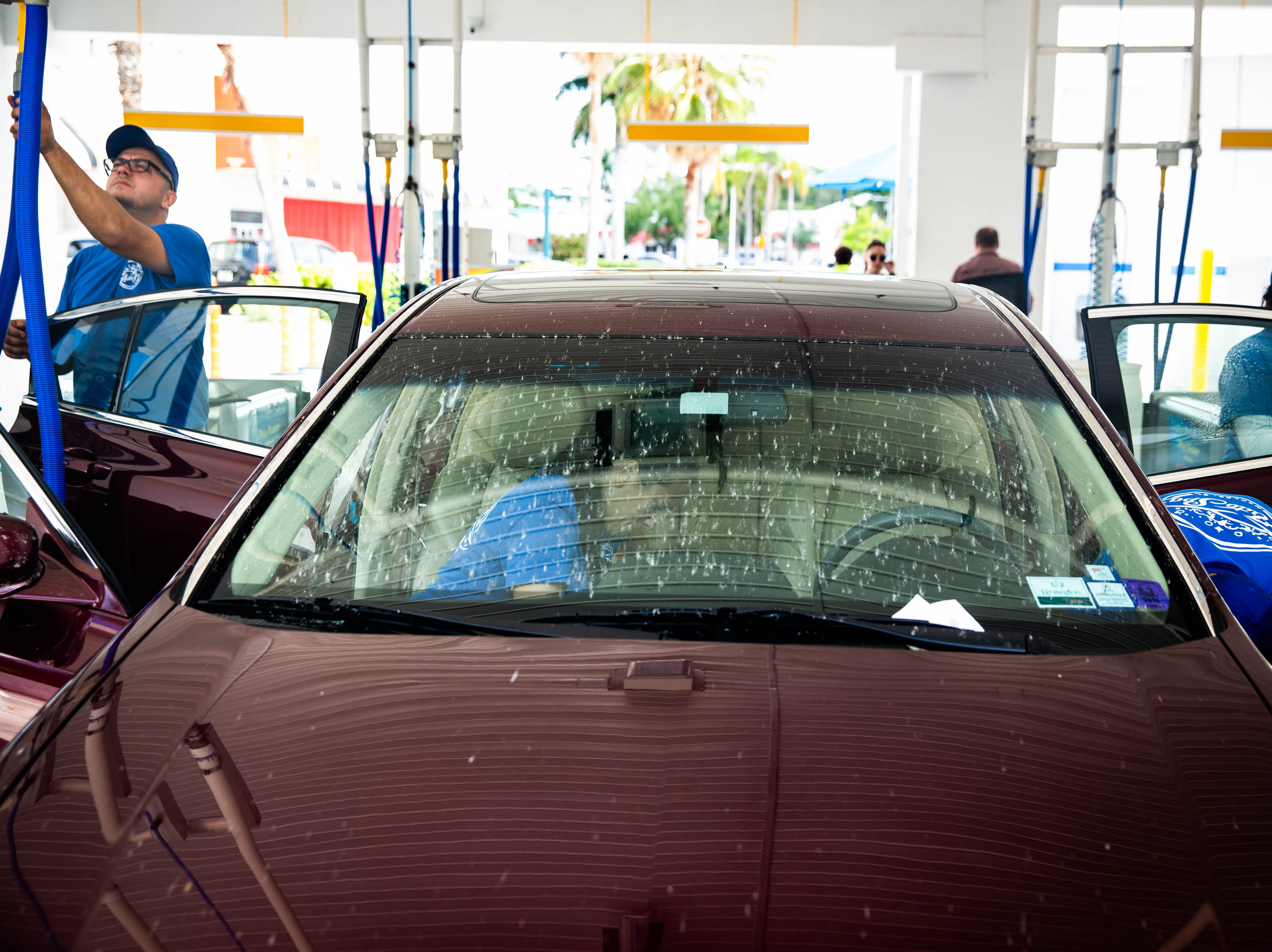 """Employees clean a line of cars at the Auto Spa car wash in Naples on Friday, May 10, 2019. The car wash has been exceptionally busy due to the presence of lovebugs in Southwest Florida. """"It's the worst we've seen in 7 years,"""" said Operations Manager Janine Ierardi."""