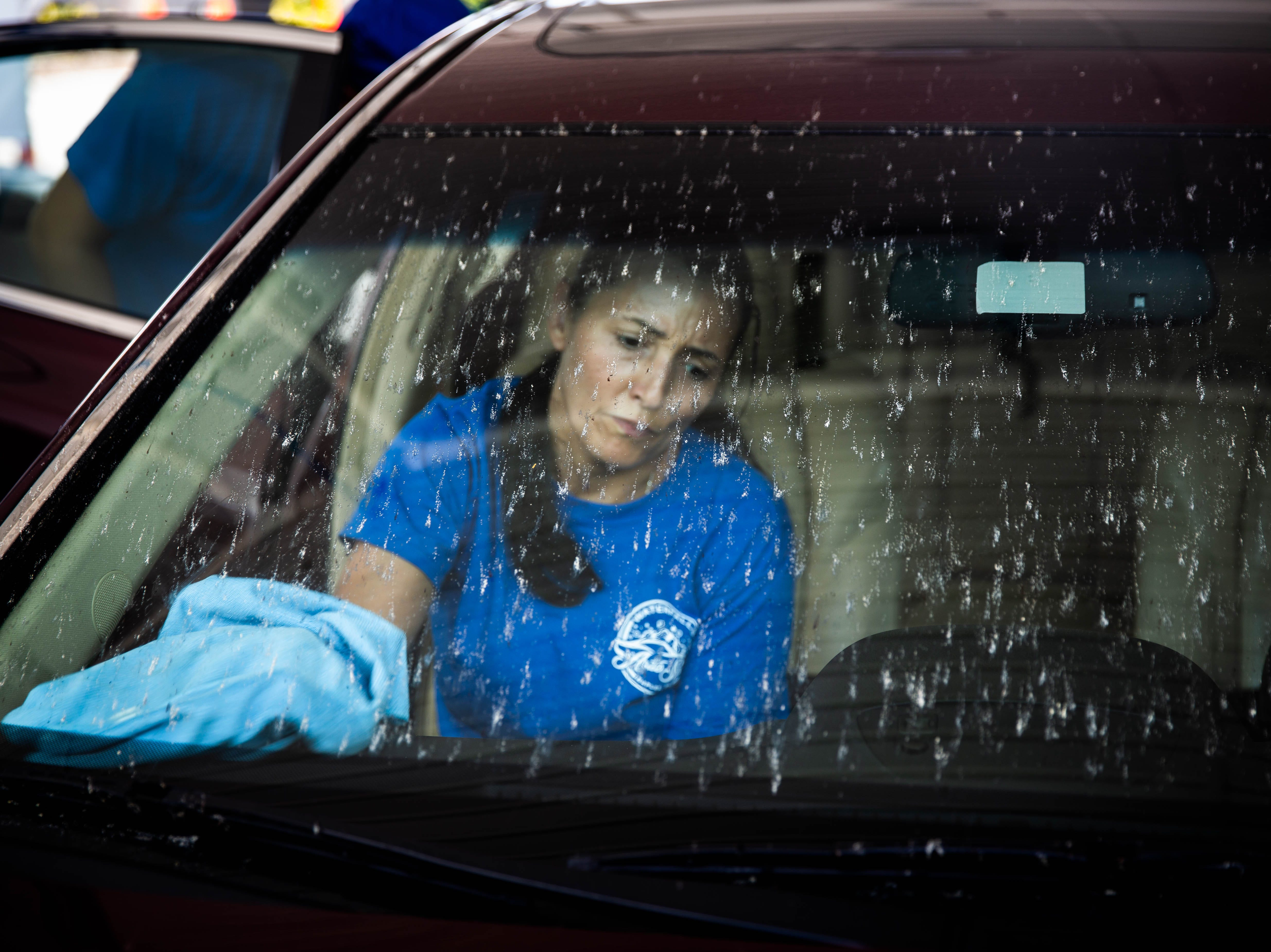 Wendy Vargan cleans lovebugs off of the windshield of a car at the Auto Spa in Naples on Friday, May 10, 2019.