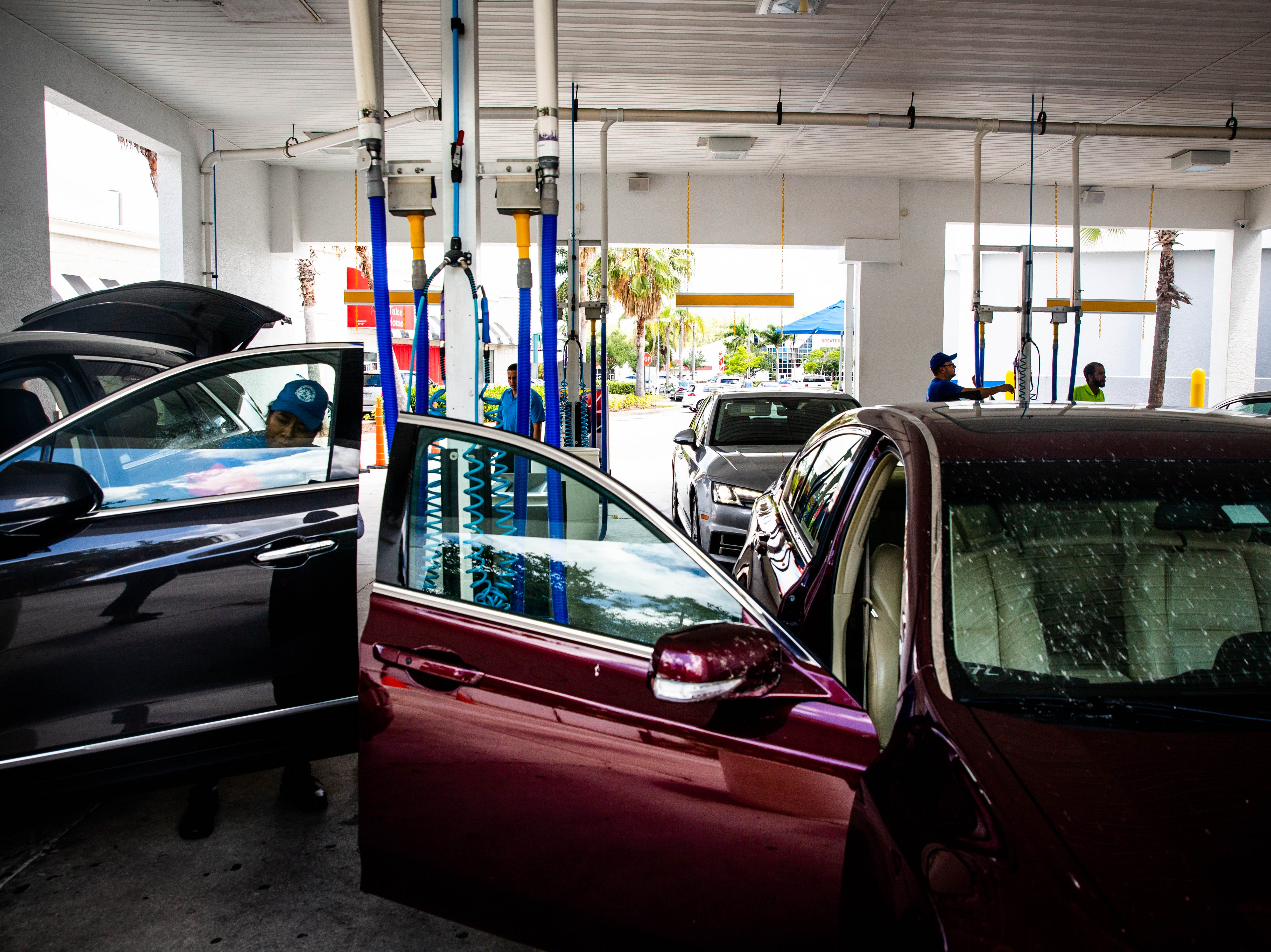 Employees clean a line of cars at the Auto Spa car wash in Naples on Friday, May 10, 2019. The car wash has been exceptionally busy due to the presence of lovebugs in Southwest Florida.