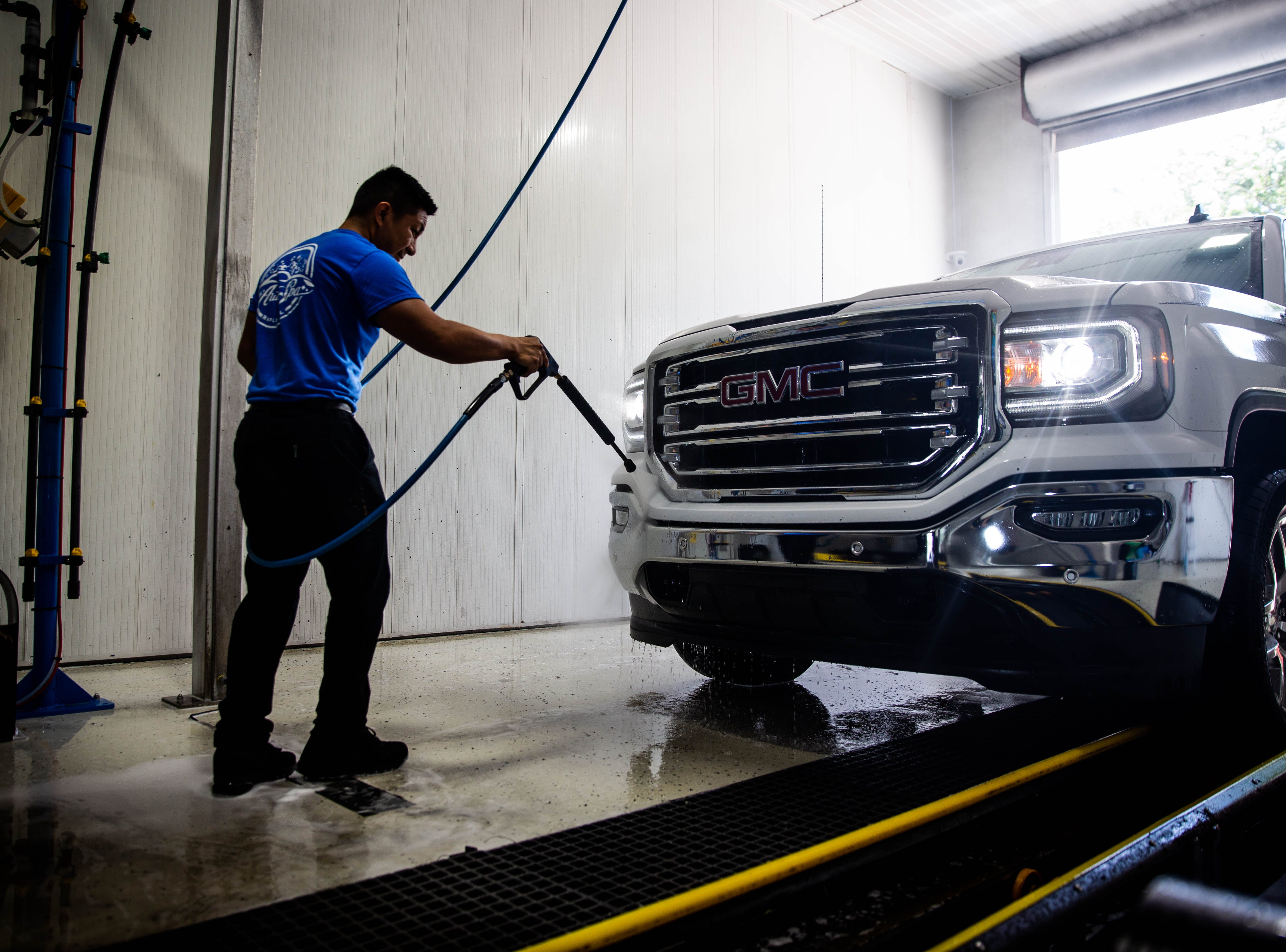 Jose Mendoza washes a truck at the Auto Spa car wash in Naples on Friday, May 10, 2019. The car wash has been exceptionally busy due to the presence of lovebugs in Southwest Florida.
