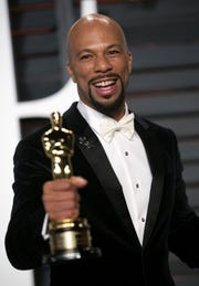 """Rapper Common, holding his Oscar for best original song for """"Glory"""" in the film """"Selma,"""" arrives for the 2015 Vanity Fair Oscar Party in this February 22, 2015."""