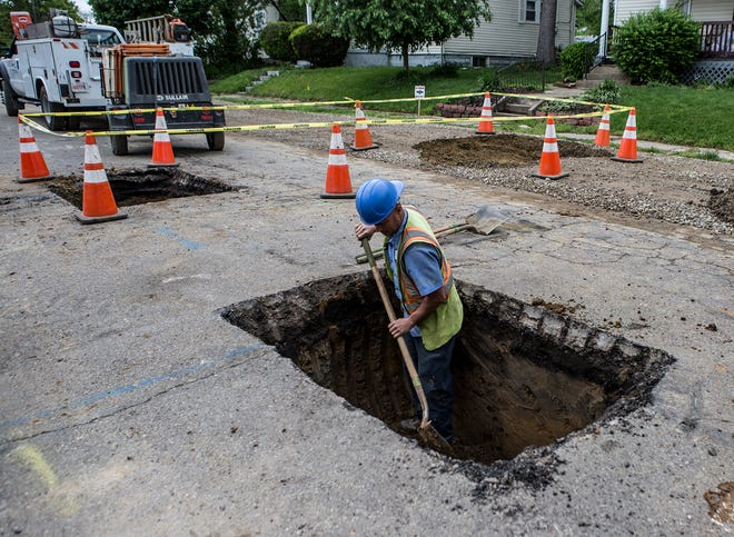 Jeremy Moore digs out the final bit of a hole so crews can finish fixing the water lines on Arlington Avenue. City utility maintenance will be one issue before the mayoral candidates this fall.