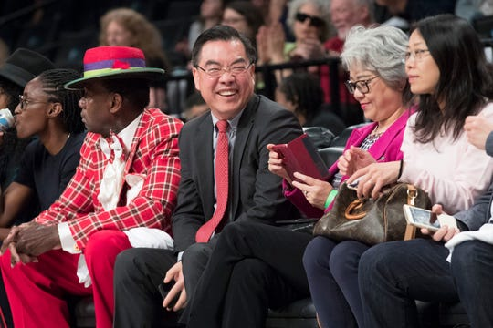 Huang Ping, center, China's consul general in New York, watches a WNBA exhibition basketball game between the New York Liberty and China, Thursday, May 9, 2019, in New York. The Liberty's new owner, Joe Tsai, saw the game as a chance to grow relations between the two countries. (AP Photo/Mary Altaffer)