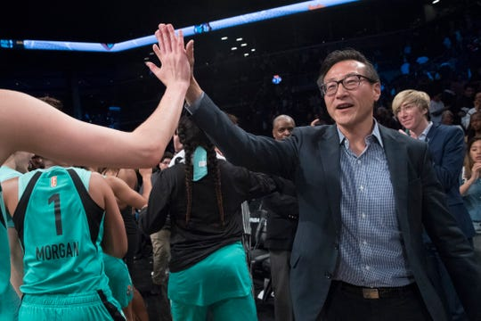 The New York Liberty's new owner, Joe Tsai, right, high-fives the Liberty players as they arrive at the bench at the end of a WNBA exhibition basketball game against China, Thursday, May 9, 2019, in New York. Tsai saw the team's exhibition game against the Chinese national team as a chance to grow relations between the two countries. (AP Photo/Mary Altaffer)