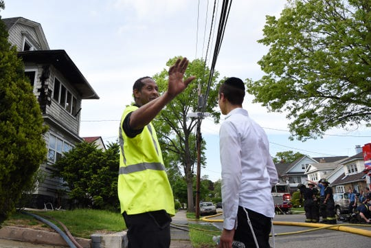 A fire is extinguished on East 39th Street in Paterson on Friday May 10, 2019. Contractor Karo Simon (left) noticed a fire as he was working in Paterson.