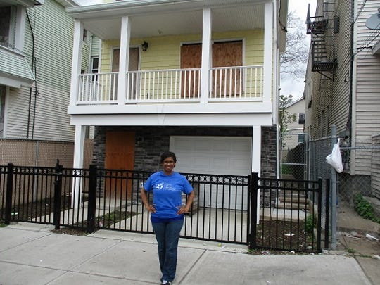 Ruth Shedrack stands on Paterson's Godwin Avenue in front of what will soon be her new home provided by Habitat for Humanity.