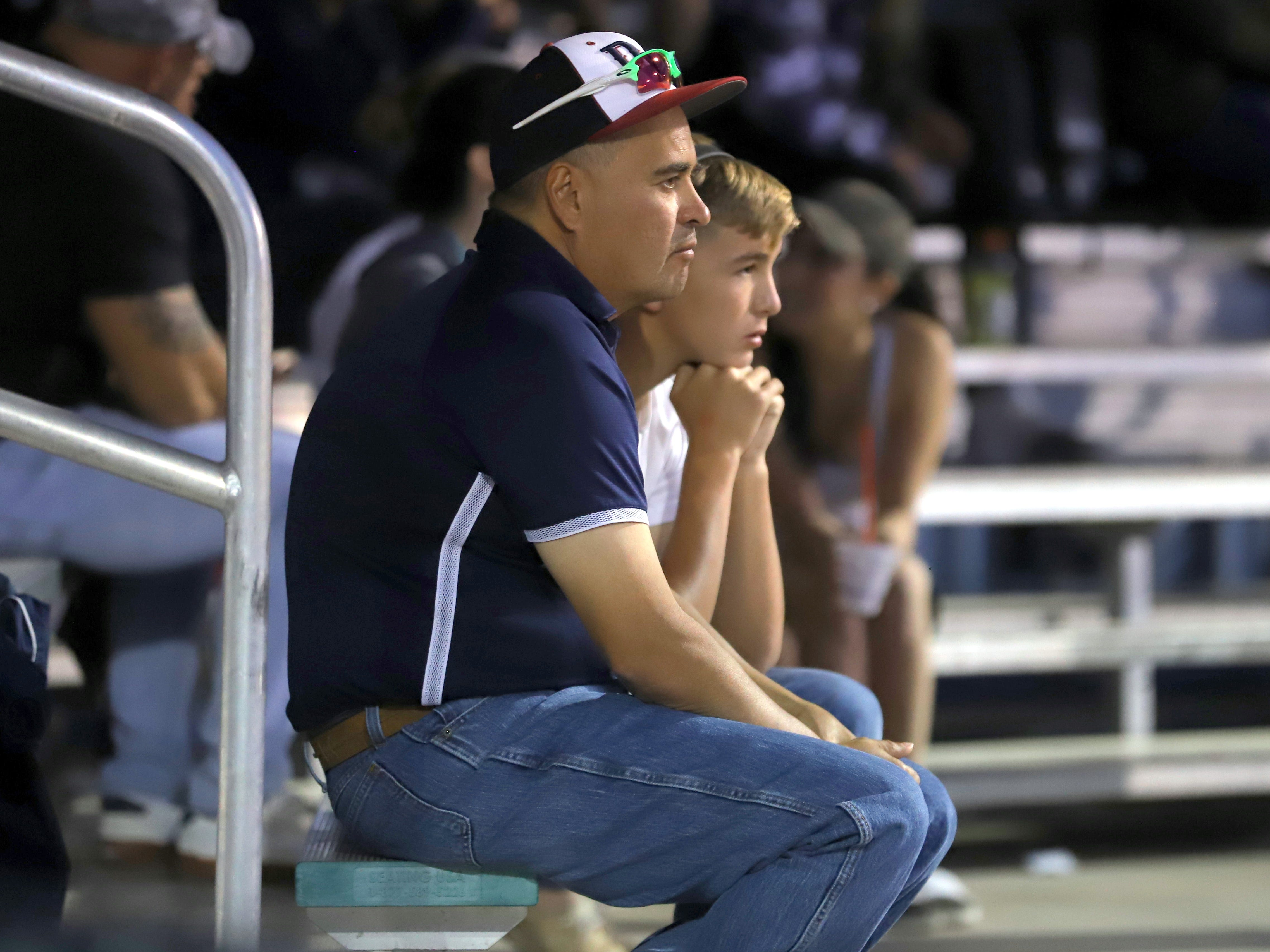 Wildcat dad Adrian Apodaca and his son   take in a tense moment in the ball game between Deming and Centennial.