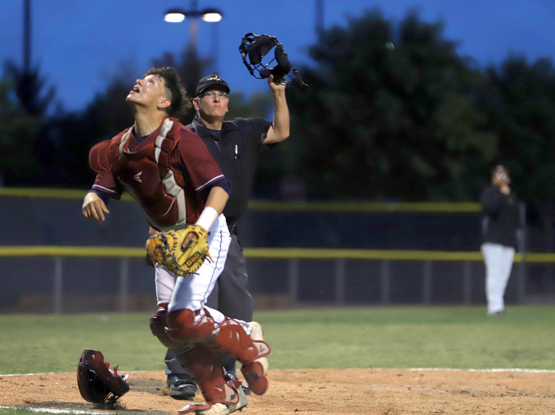 Senior Wildcat catcher Robert Ruiz looks for the pop foul while home plate umpire Ben Vega looks on.