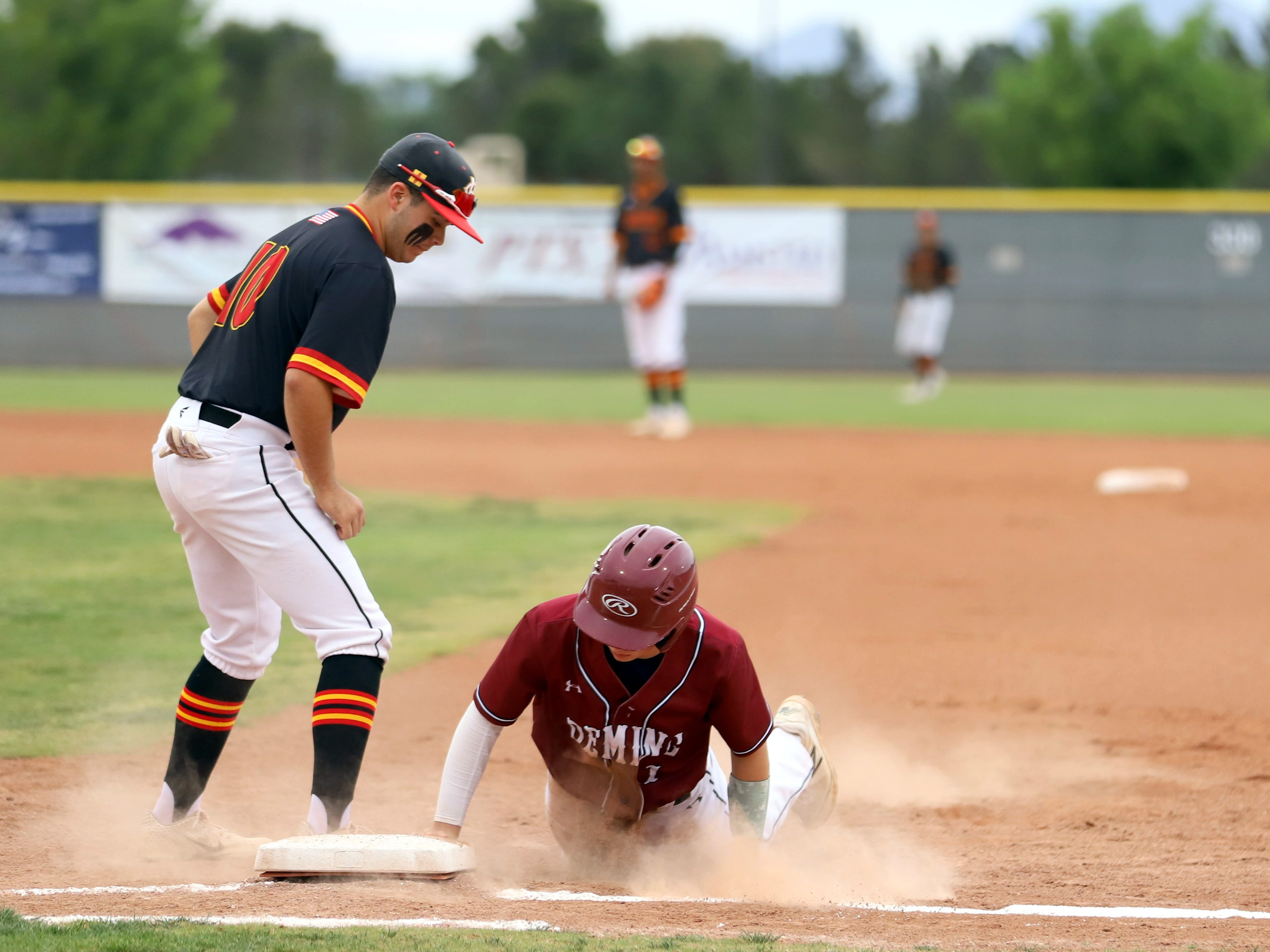 Junior Creighton Apodaca (1) dived back to first base to avoid the pick-off attempt from Centennial pitcher Wilson Bannister.