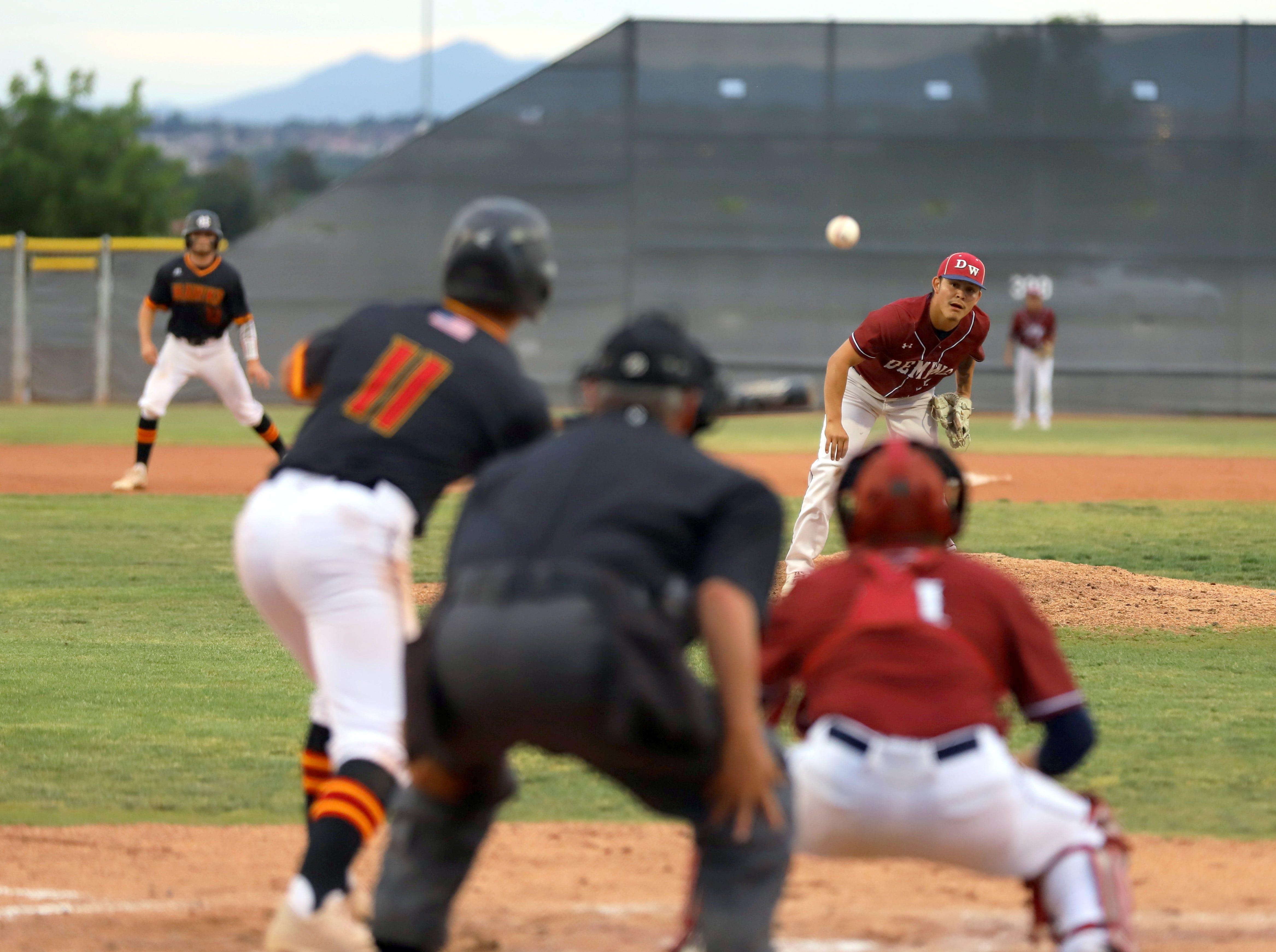 Junior Wildcat pitcher Fernie Munoz peers in after the pitch as Centennial batter Adrian Hernandez squares to bunt.
