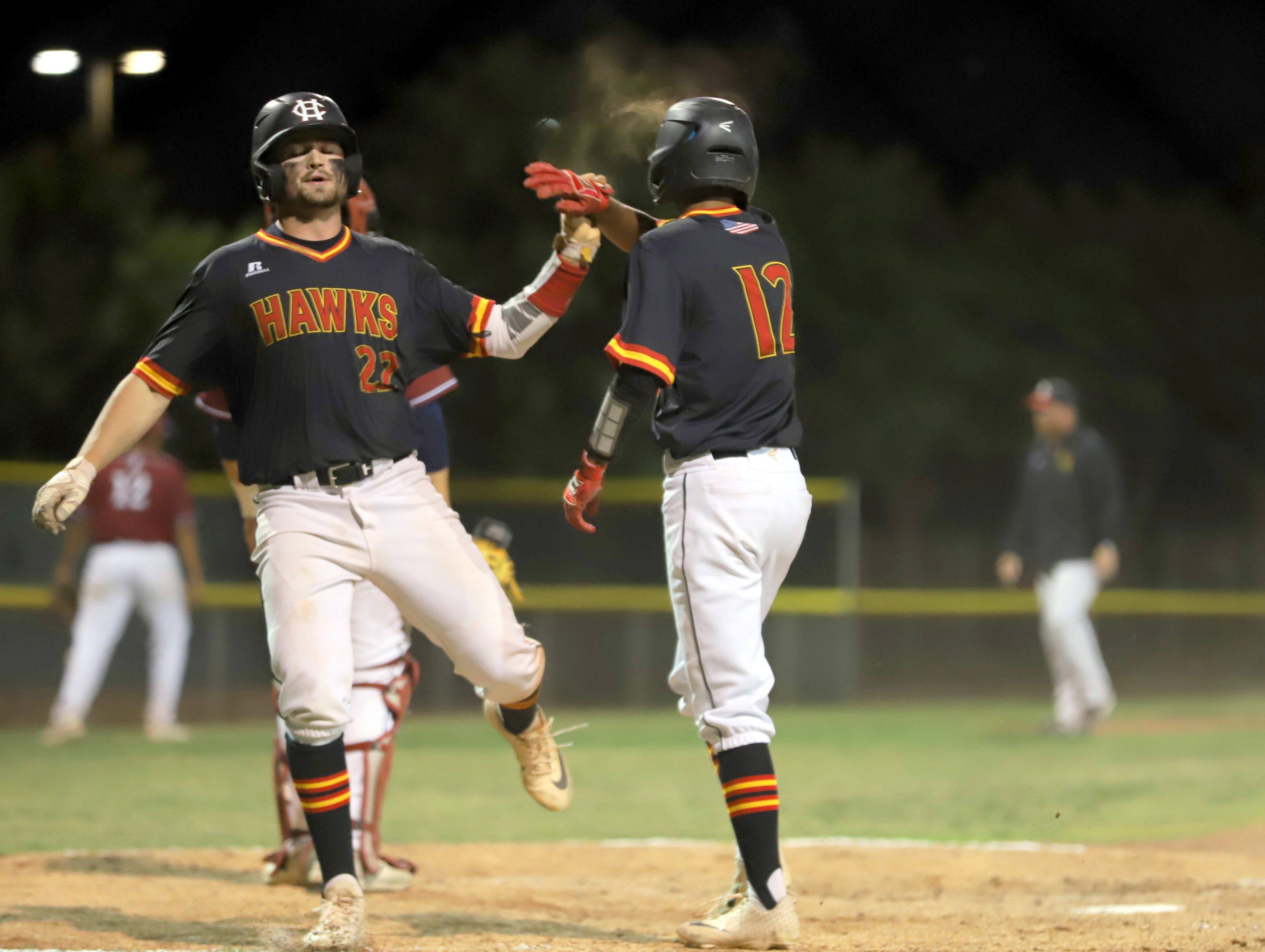 Centennial slugger Lance Frost (22) is greeted at home plate with a high-five from teammate Fernando Loera (17).