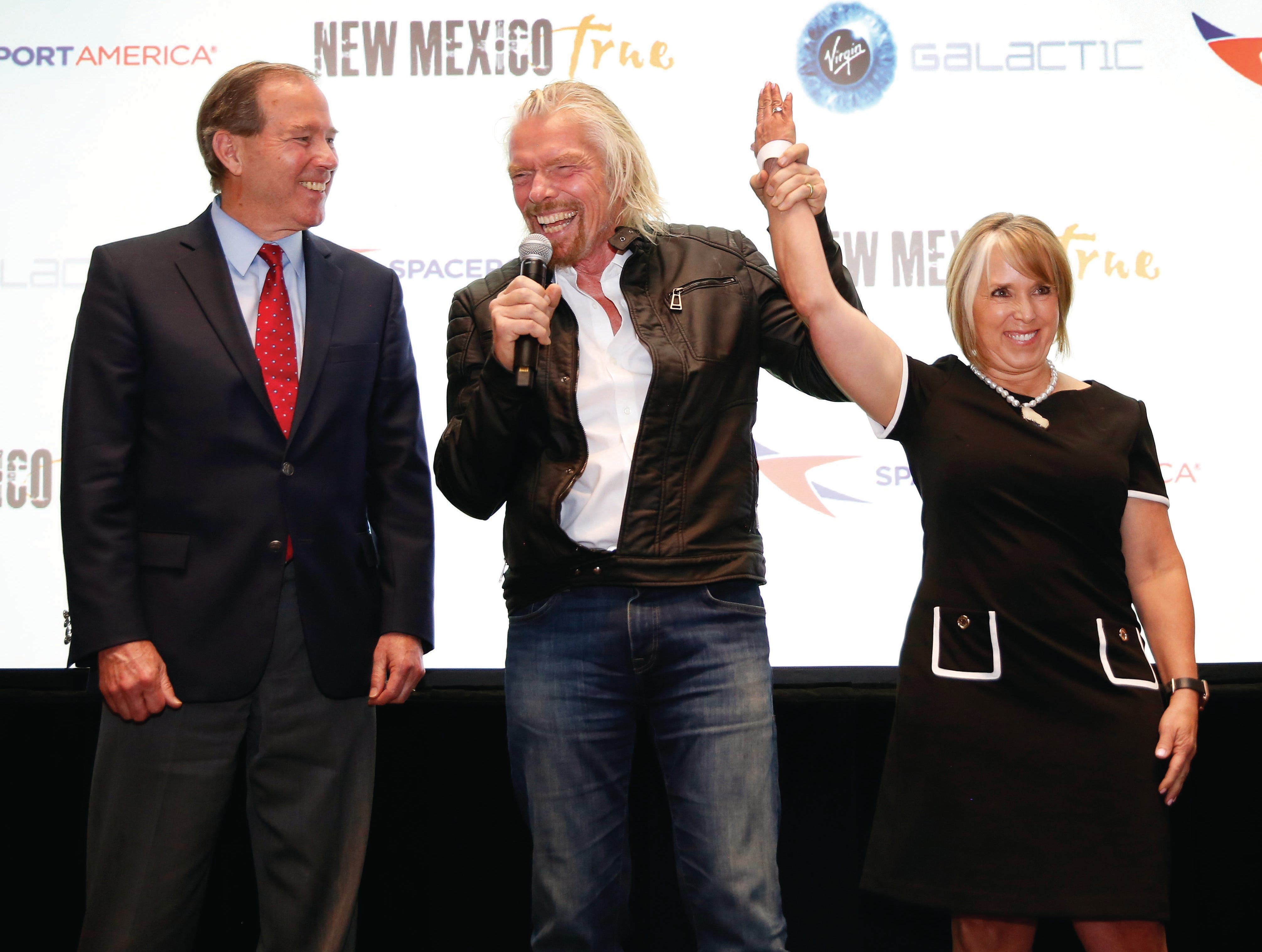Virgin Galactic's Richard Branson, center, celebrates the space company's announcement with New Mexico Gov. Michelle Lujan Grisham and U.S. Sen. Tom Udall, D-N.M., on Friday, May 10, 2019.