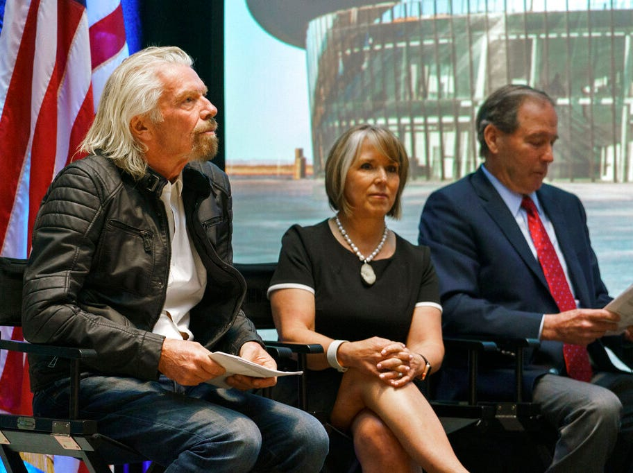 Virgin Galactic founder Richard Branson, left, New Mexico Gov. Michelle Lujan Grisham and U.S. Sen. Tom Udall wait to speak during an event at the state capital on Friday, May 10, 2019, in Santa Fe, N.M.  Branson announced Friday that his company will begin shifting operations from California to a spaceport and specialized runway in the New Mexico desert in final preparations for commercial flights.