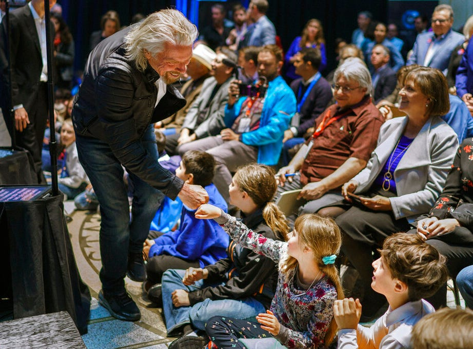 Virgin Galactic founder Richard Branson, gives a fist bump to Sonia Thorp, 9, of Carlos Gilbert Elementary at the beginning of an event at the state capital on Friday, May 10, 2019, in Santa Fe, N.M.  Branson announced Friday that his company will begin shifting operations from California to a spaceport and specialized runway in the New Mexico desert in final preparations for commercial flights.