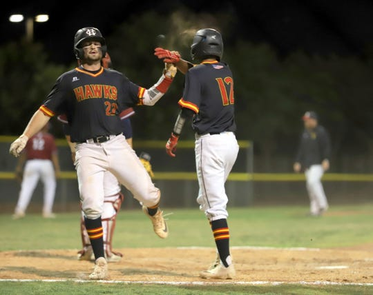 Lance Frost (22) gets a high-five from teammate Fernando Loera (12) after crossing home plate during Thursday's 10-0 Class 5A Playoff win over Deming High at the Field of Dreams.