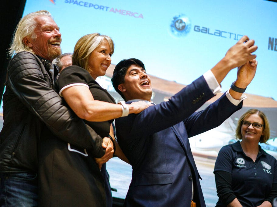 Virgin Galactic founder Sir Richard Branson picks up New Mexico Gov. Michelle Lujan Grisham while the company's Kevin Prieto takes a selfie during an event announcing Virgin Galactic's move to New Mexico Friday, May 10, 2019, at the state capital in Santa Fe, N.M. The company says is it nearing the first commercial flights from the Spaceport America.
