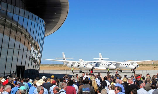In this Oct. 17, 2011, file photo a crowd gathers outside Spaceport America for a dedication ceremony as Virgin Galactic's mothership WhiteKnightTwo sits on the tarmac. British billionaire Richard Branson is taking another concrete step toward offering rides into the close reaches of space for paying passengers. Branson announced Friday, May 10, 2019, that Virgin Galactic will immediately begin shifting operations from California to a spaceport and specialized runway in the New Mexico desert in final preparations for commercial flights.