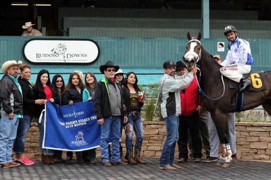 The winning horse No Mires a La Luna and his owners pose after the first race of Friday's Maiden Stakes Trials at the Ruidoso Downs in Ruidoso.