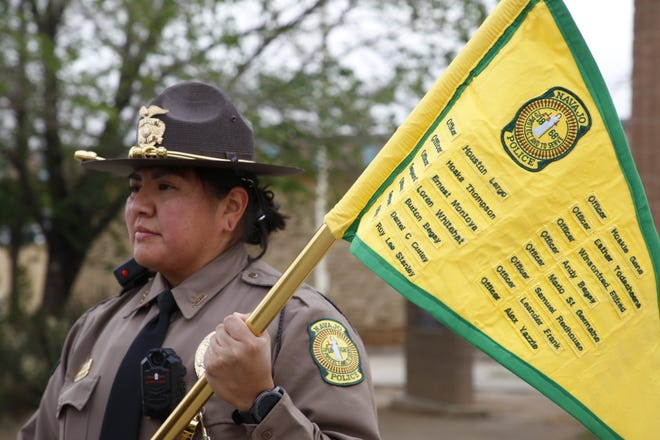 Navajo Police Officer Danielle Murdock holds a flag on May 10 that lists the names of Navajo police officers who died in the line of duty.