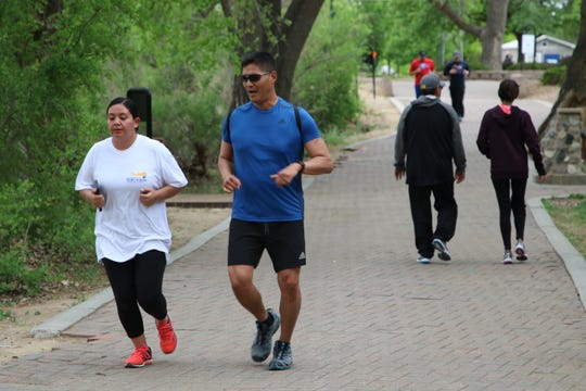 Farmington Police officers Alma Chavez, left, and Craig Yazzie, center, run through Berg Park on May 9. Officers will have an increased presence at the park following a fatal stabbing that happened on May 5.