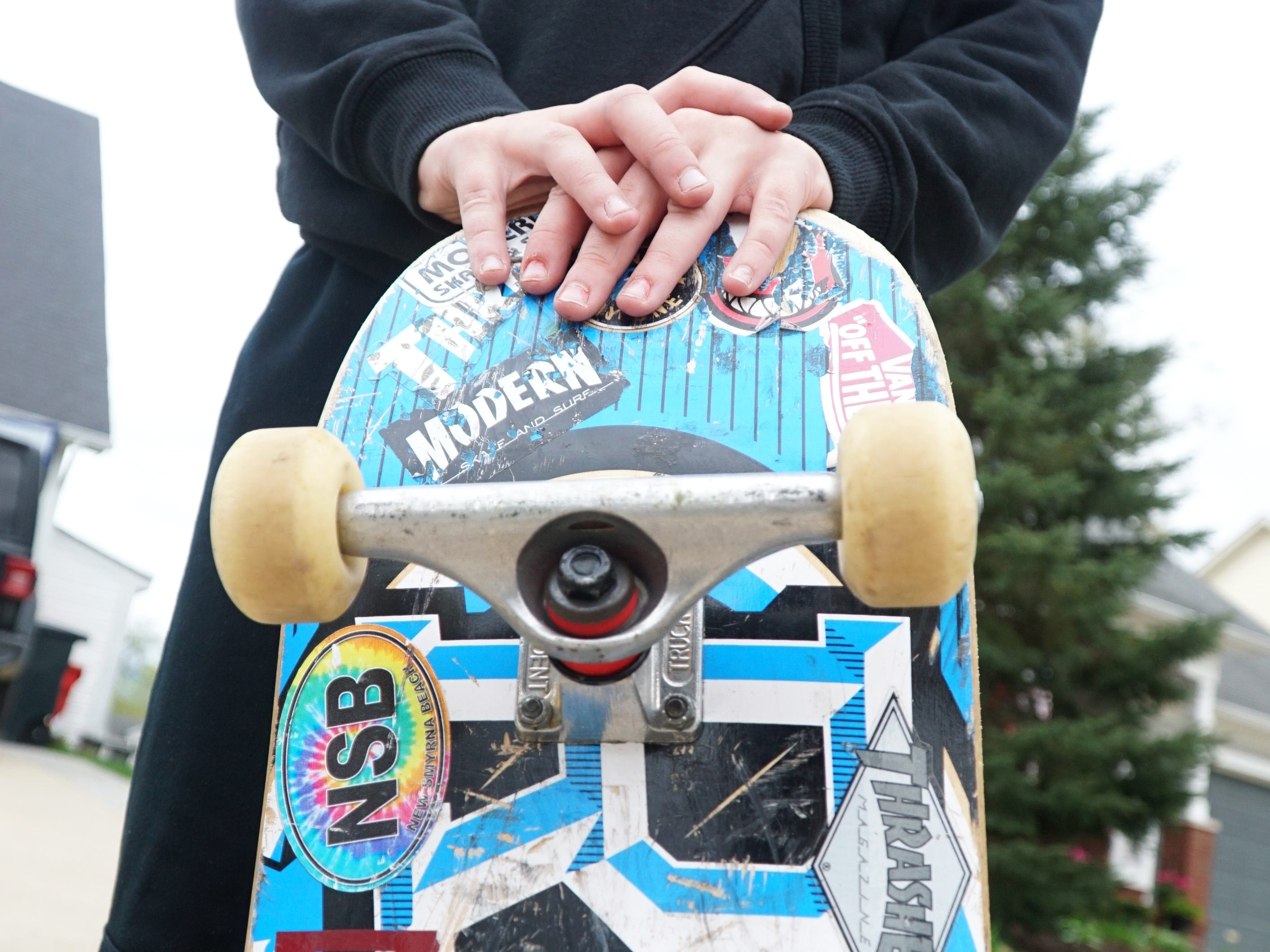 Duke Stempien, 11, with his much sticker-covered skateboard.
