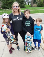 Milford's Kristi Stempien is hoping the village will construct a skateboard park so that her kids don't have to worry about skating in the street - with its dangerous traffic. From left are some of her army of four and two-wheeled artists including hwer kids Lovey, 9, and Duke, 11, and neighborhood friend Joey Musialowski, 6, at far right.