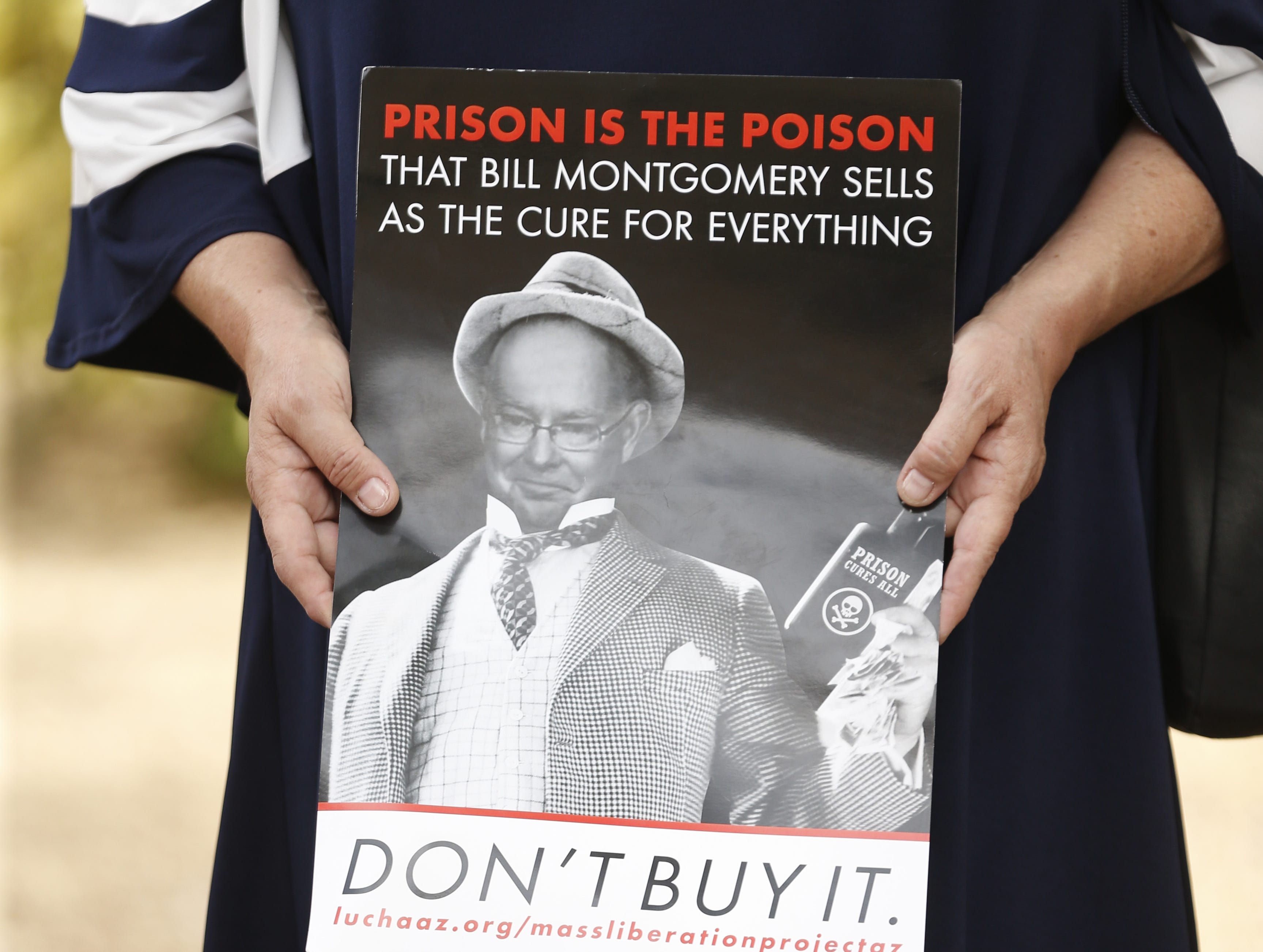 "Chimene Hawes holds a sign stating ""Prison is the Poison"" during a protest against cash bail at the Maricopa County Attorney's office in Phoenix on May 9, 2019."