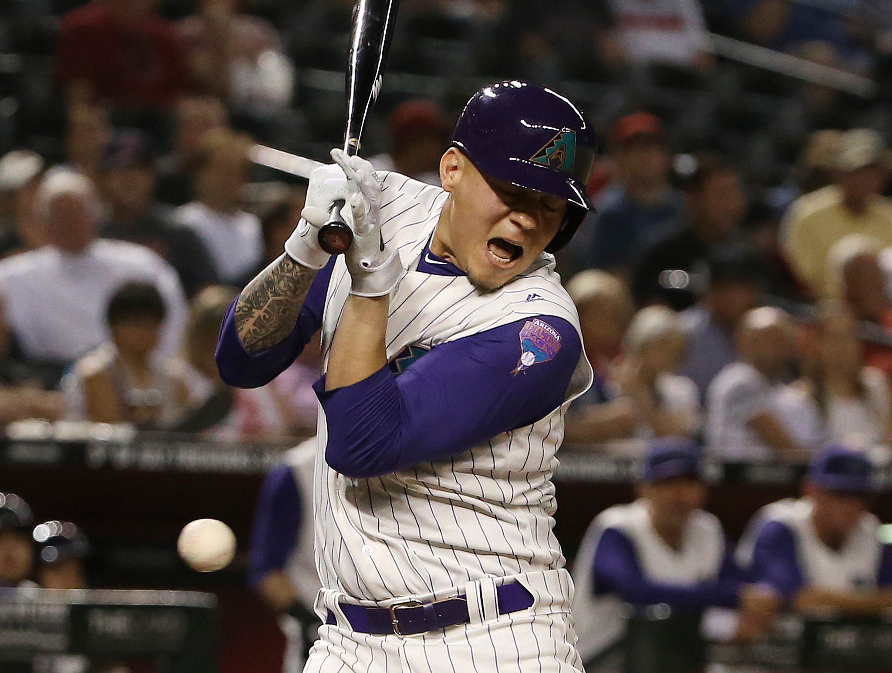 Arizona Diamondbacks' Wilmer Flores grimaces after being hit by a pitch thrown by Atlanta Braves starter Mike Soroka during the sixth inning of a baseball game Thursday, May 9, 2019, in Phoenix. (AP Photo/Ross D. Franklin)