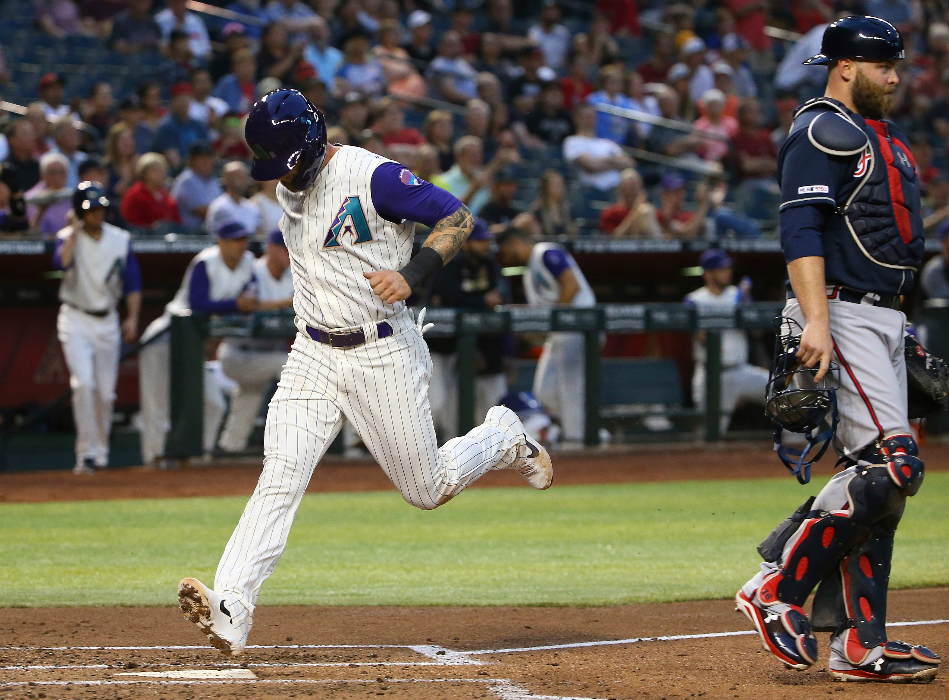 Arizona Diamondbacks' Christian Walker, left, scores a run as Atlanta Braves catcher Brian McCann, right, watches the movement of the ball during the second inning of a baseball game Thursday, May 9, 2019, in Phoenix. (AP Photo/Ross D. Franklin)
