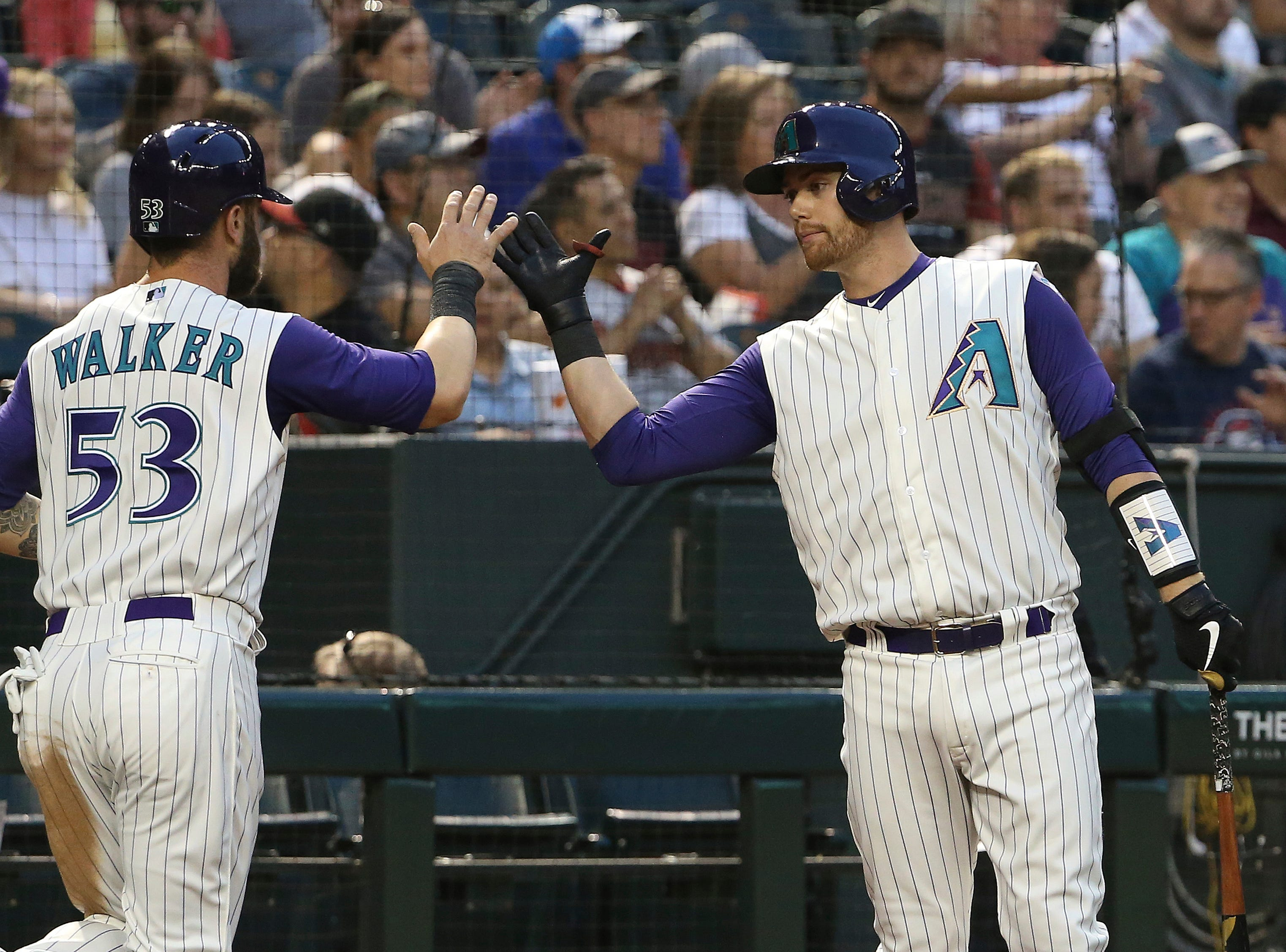 Arizona Diamondbacks' Christian Walker (53) celebrates his run scored against the Atlanta Braves with Carson Kelly, right, during the second inning of a baseball game Thursday, May 9, 2019, in Phoenix. (AP Photo/Ross D. Franklin)