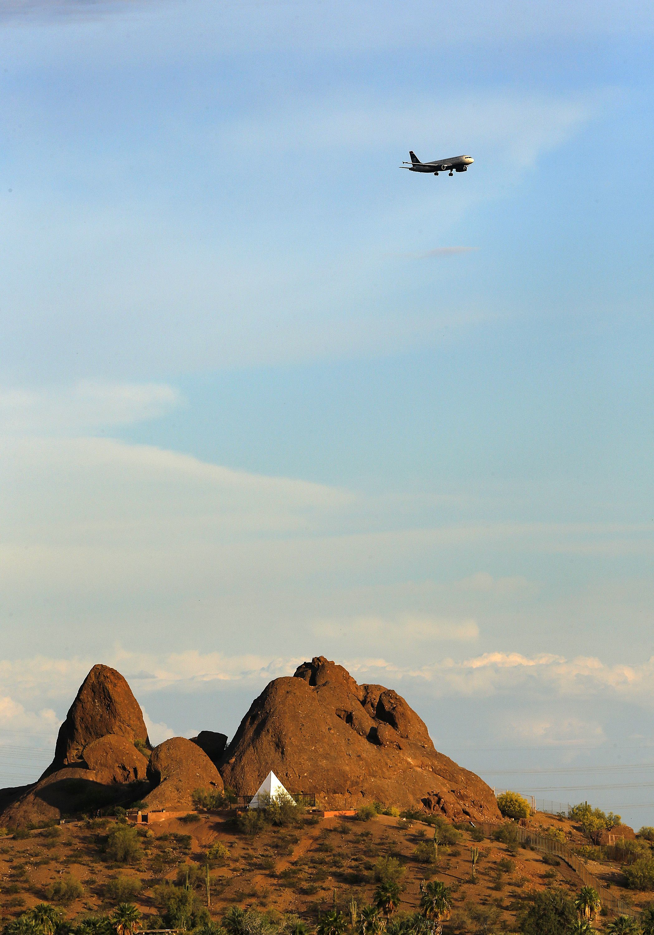 A jet makes its final approach above Hunt's Tomb in Papago Park on April 19, 2014, at Papago Park.