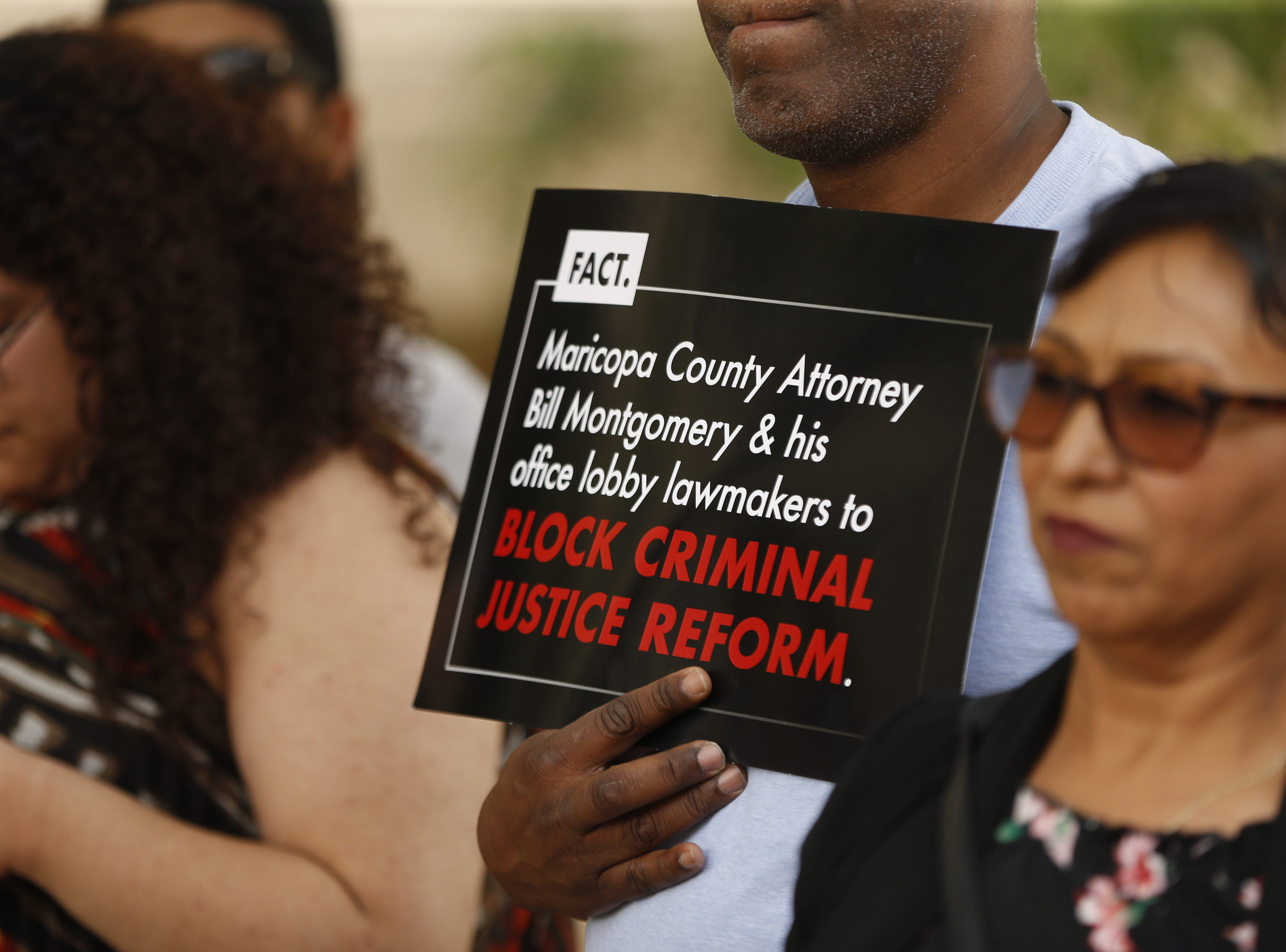 People hold signs during a protest against cash bail at the Maricopa County Attorney's office in Phoenix on May 9, 2019.