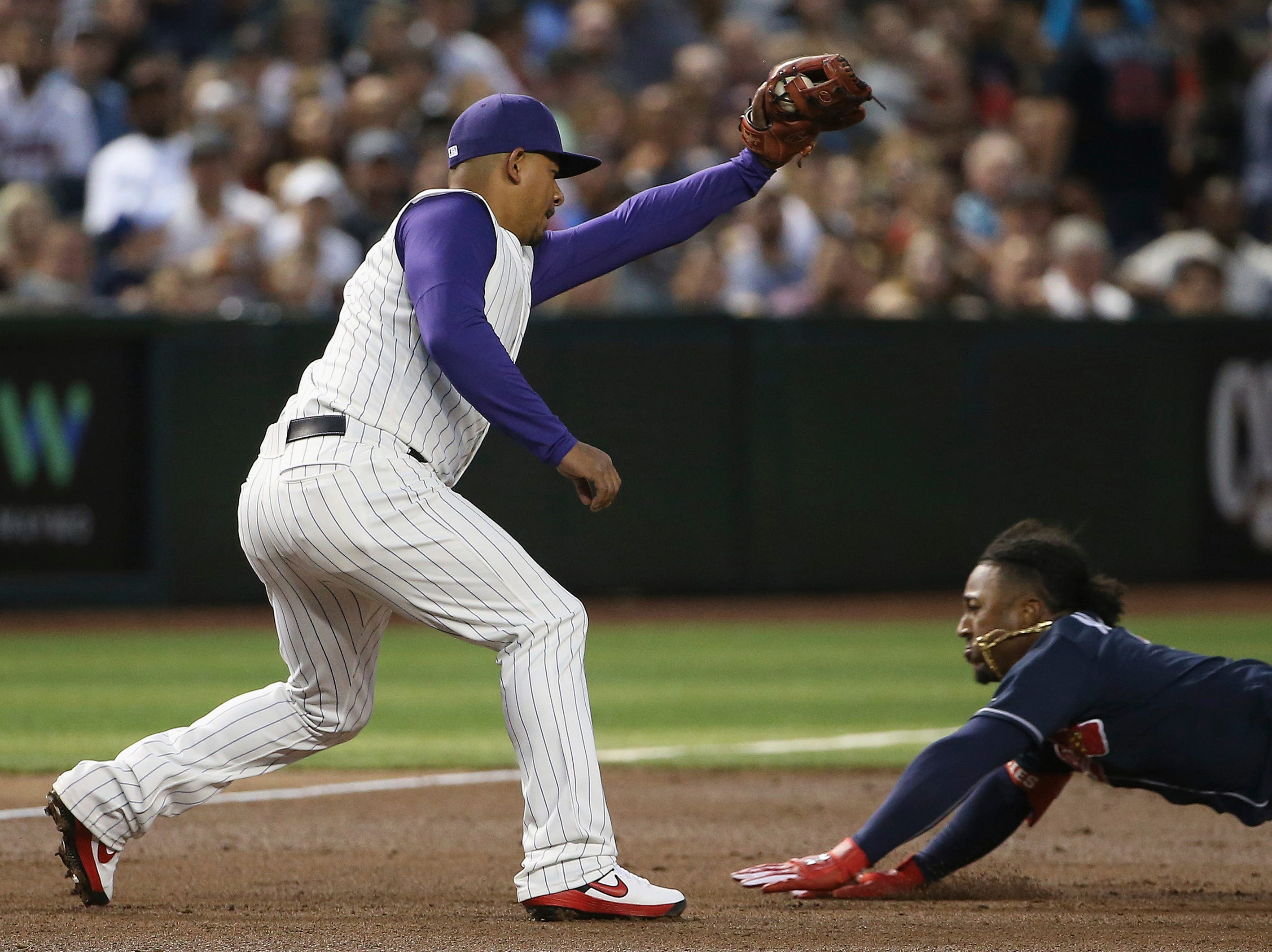 Arizona Diamondbacks third baseman Eduardo Escobar, left, makes a catch before tagging out Atlanta Braves' Ozzie Albies at third base as Albies tried to stretch a double into a triple during the third inning of a baseball game Thursday, May 9, 2019, in Phoenix. (AP Photo/Ross D. Franklin)