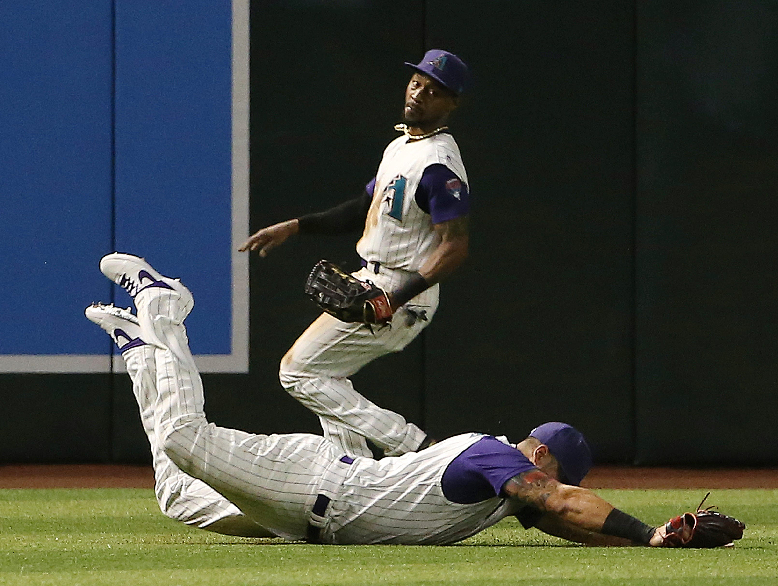 Arizona Diamondbacks left fielder David Peralta, front, makes a diving catch on a line drive hit by Atlanta Braves' Nick Markakis, while center fielder Jarrod Dyson, back, watches during the seventh inning of a baseball game Thursday, May 9, 2019, in Phoenix. (AP Photo/Ross D. Franklin)