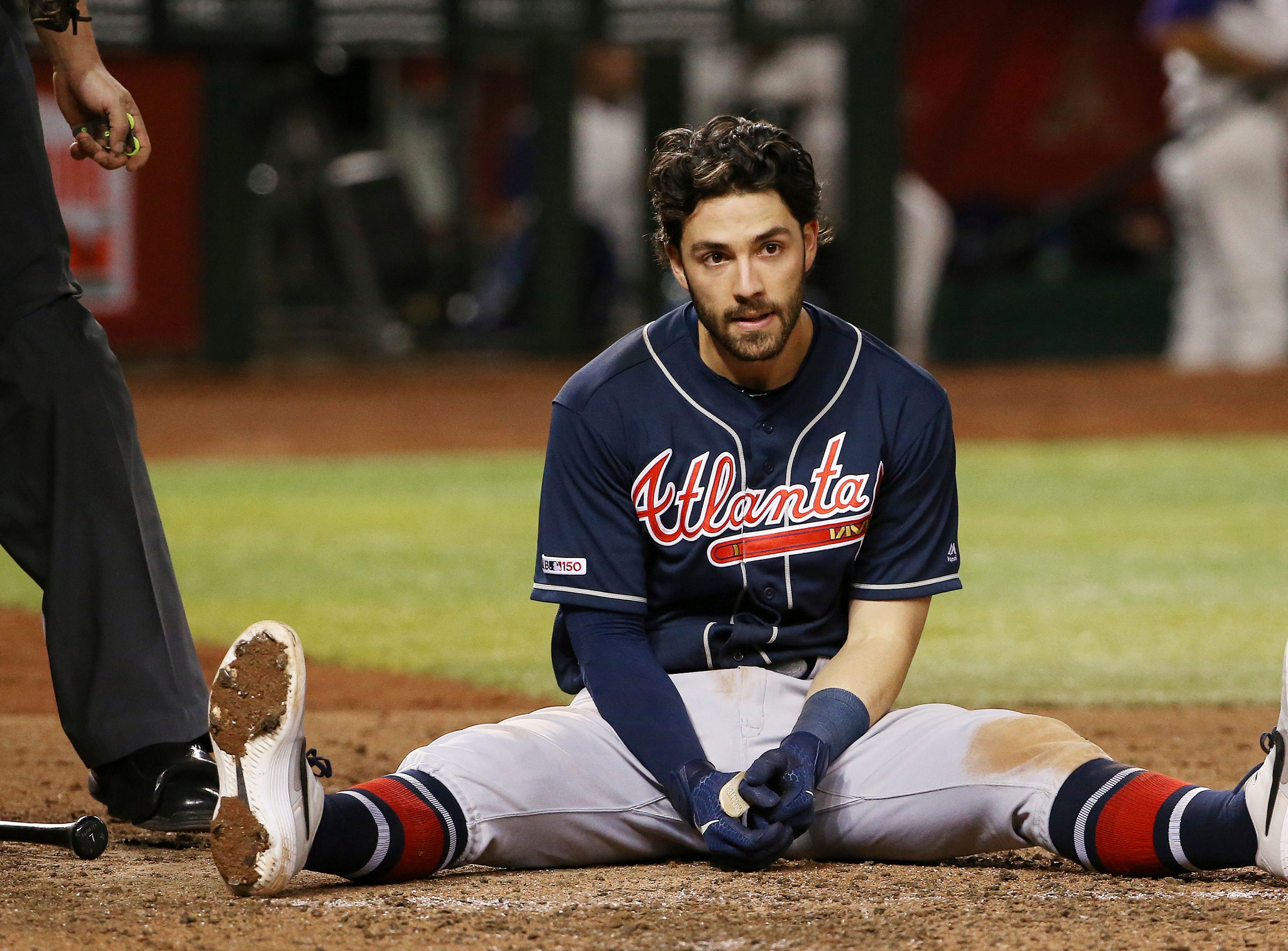 Atlanta Braves' Dansby Swanson sits on the ground after fouling off a pitch that nearly hit him during the seventh inning of the team's baseball game against the Arizona Diamondbacks on Thursday, May 9, 2019, in Phoenix. (AP Photo/Ross D. Franklin)