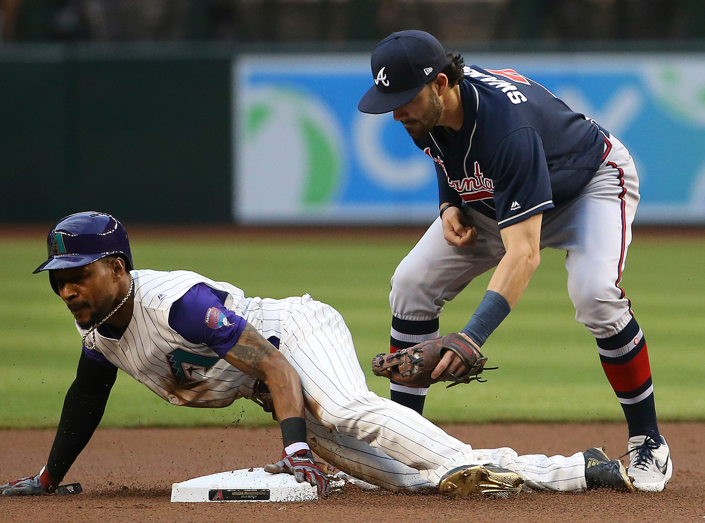 Arizona Diamondbacks' Jarrod Dyson, left, steals second base as Atlanta Braves shortstop Dansby Swanson, right, applies a late tag during the first inning of a baseball game Thursday, May 9, 2019, in Phoenix. (AP Photo/Ross D. Franklin)