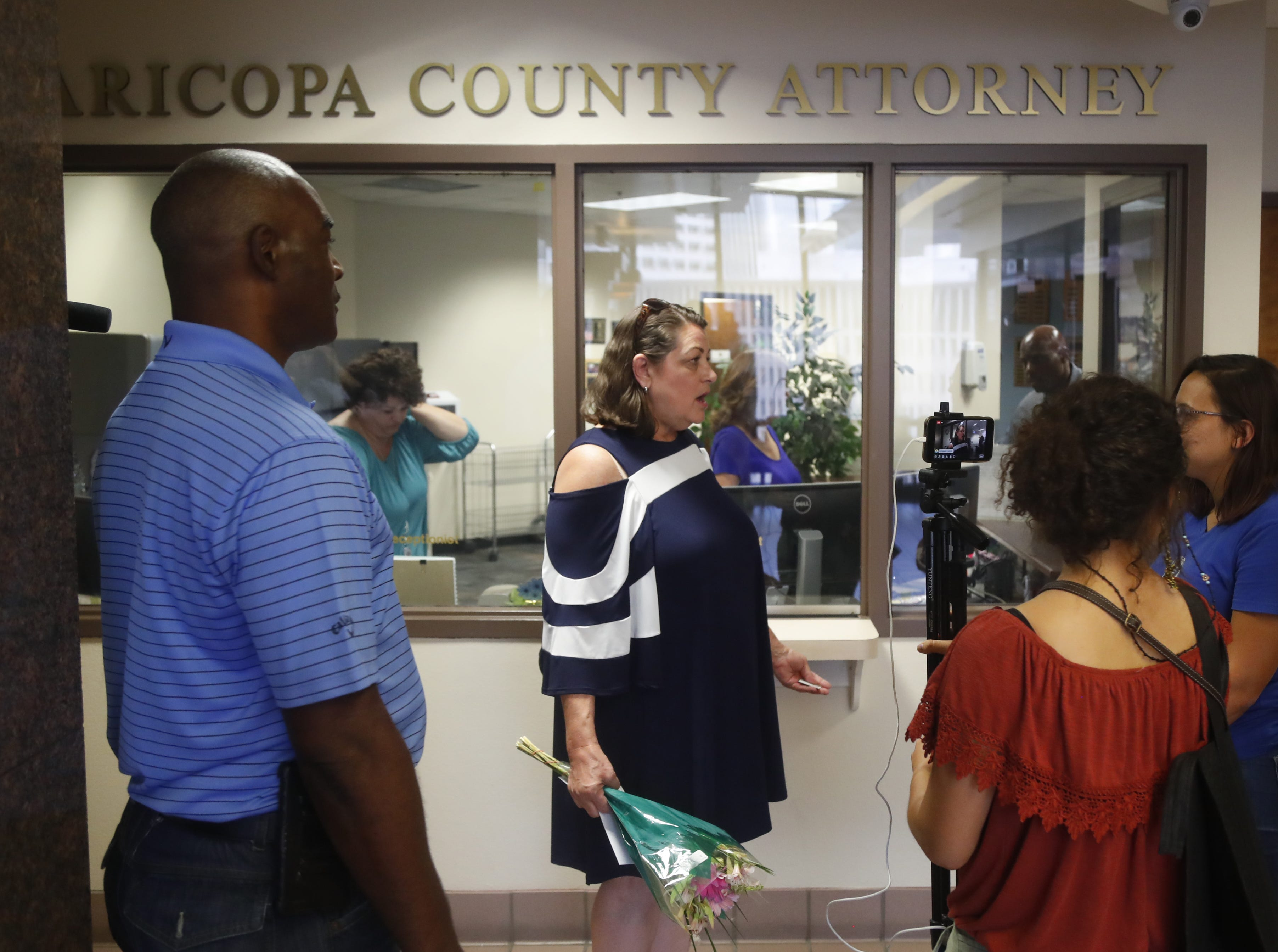 Chimene Hawes (L) speaks with Nicole Hale as they wait to speak with Maricopa County Attorney Bill Montgomery during a protest against cash bail at the Maricopa County Attorney's office in Phoenix on May 9, 2019.