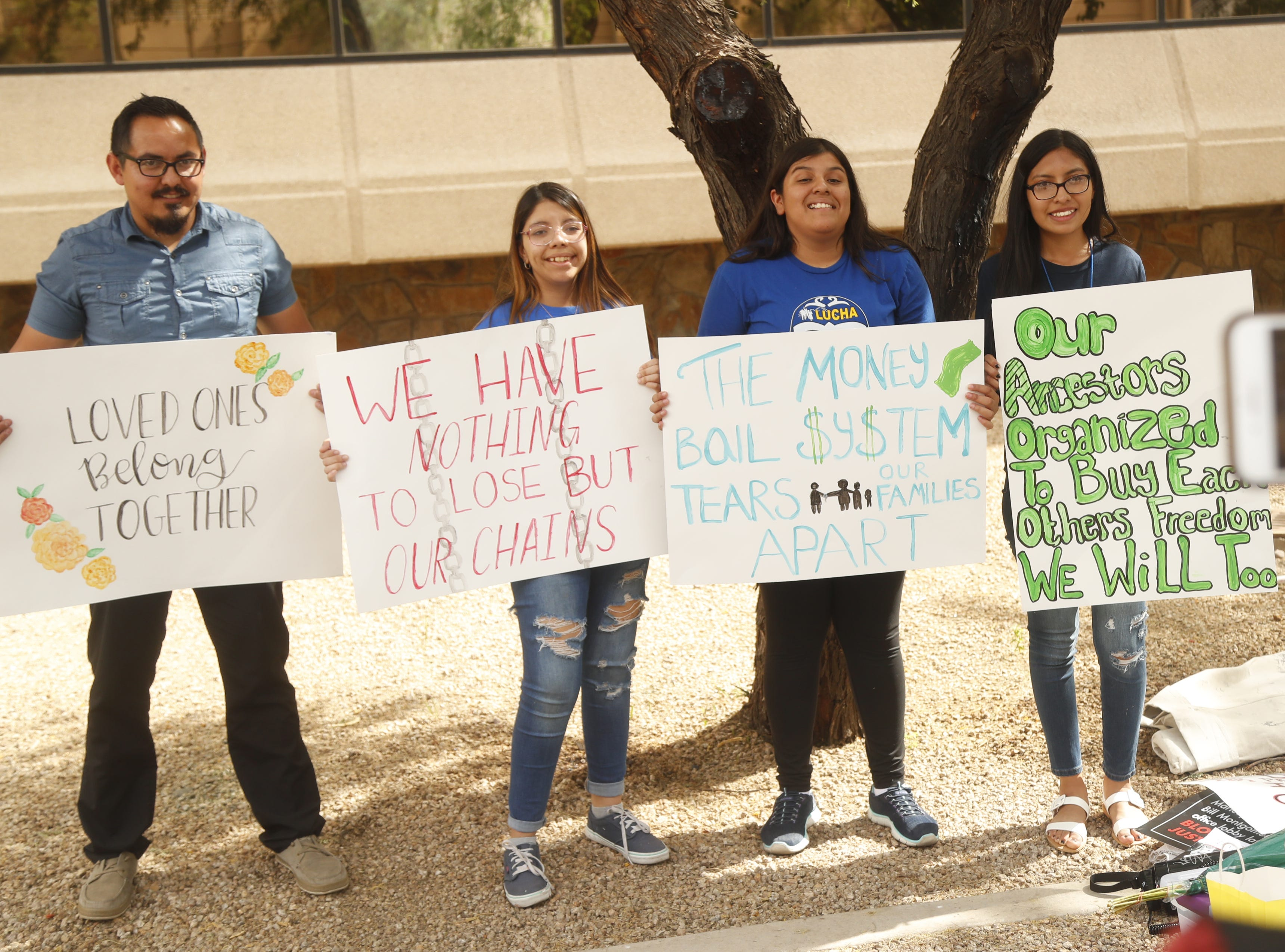 Aldo Gonzalez (L-R), Annette Alvarez, Ivonne Dominguez and Giovana Reyes hold signs during a protest against cash bail at the Maricopa County Attorney's office in Phoenix on May 9, 2019.