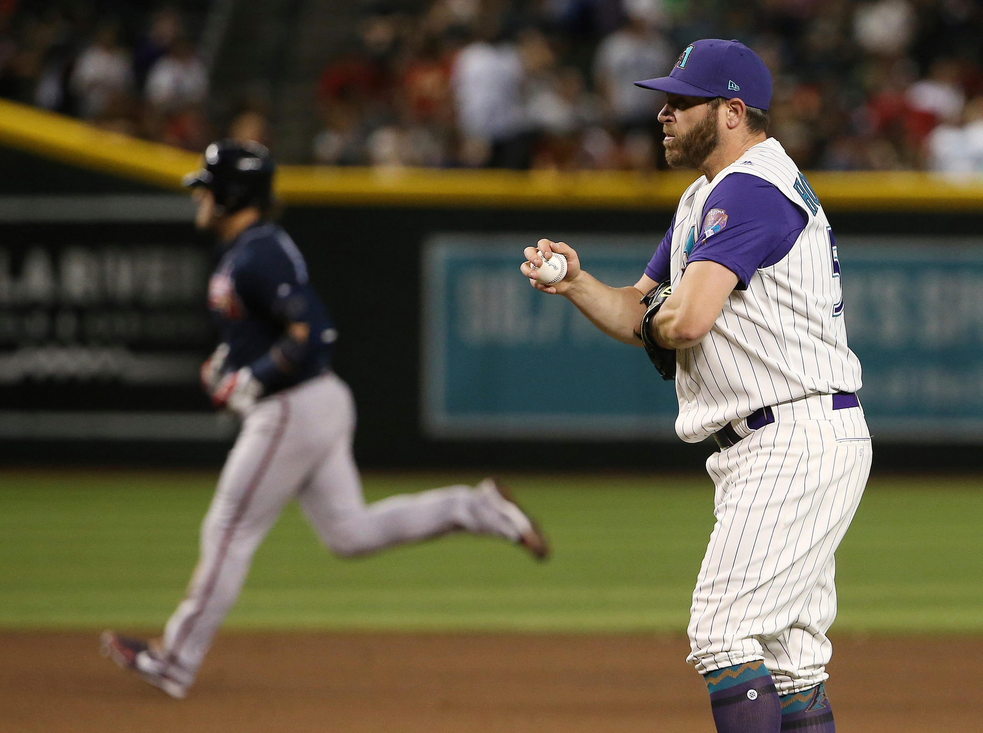 Arizona Diamondbacks relief pitcher Greg Holland, right, gets a new baseball after giving up a home run to Atlanta Braves' Josh Donaldson, left, during the ninth inning of a baseball game Thursday, May 9, 2019, in Phoenix. (AP Photo/Ross D. Franklin)