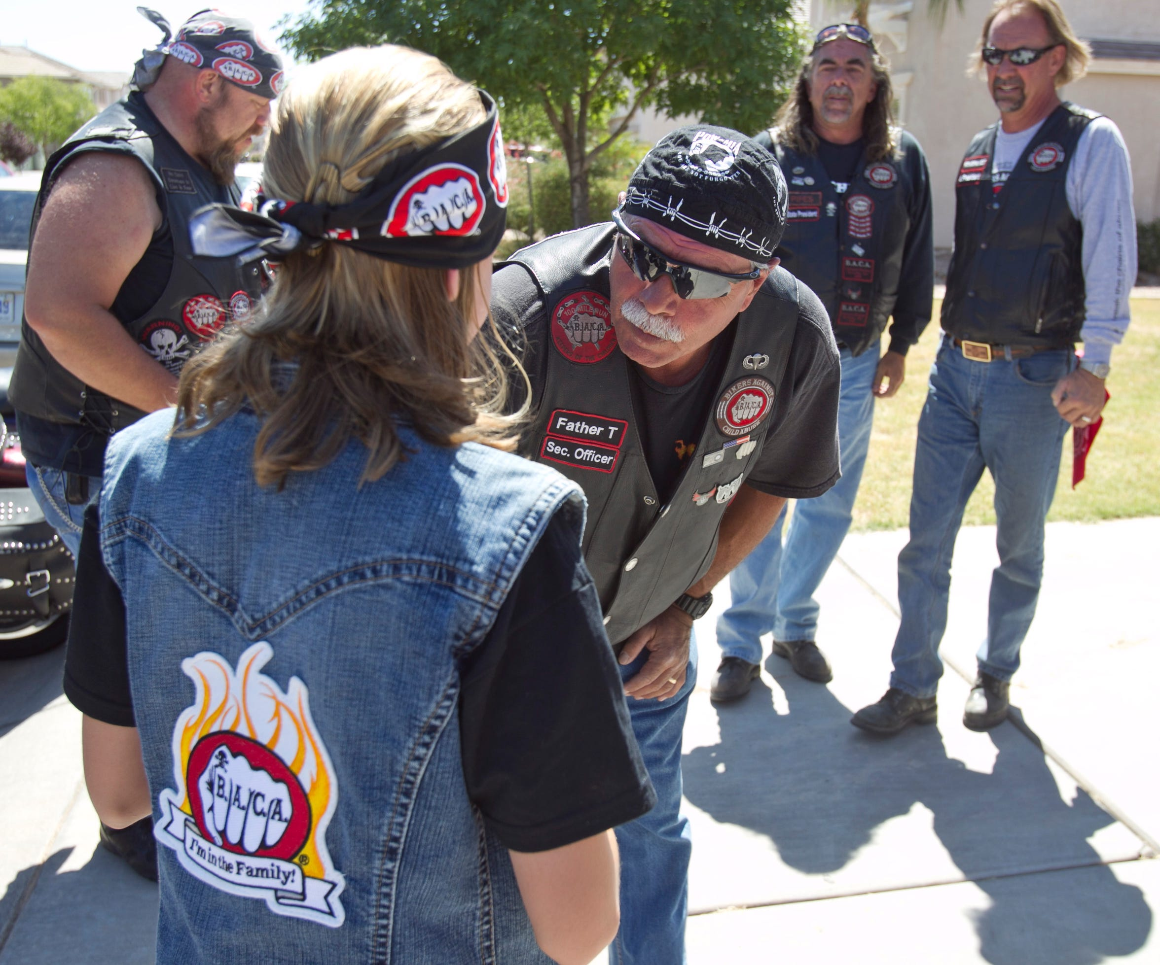 "Father T and other members of the Arizona chapter of Bikers Against Child Abuse International wear their motto on their black leather vests and T-shirts: ""No child deserves to live in fear."""