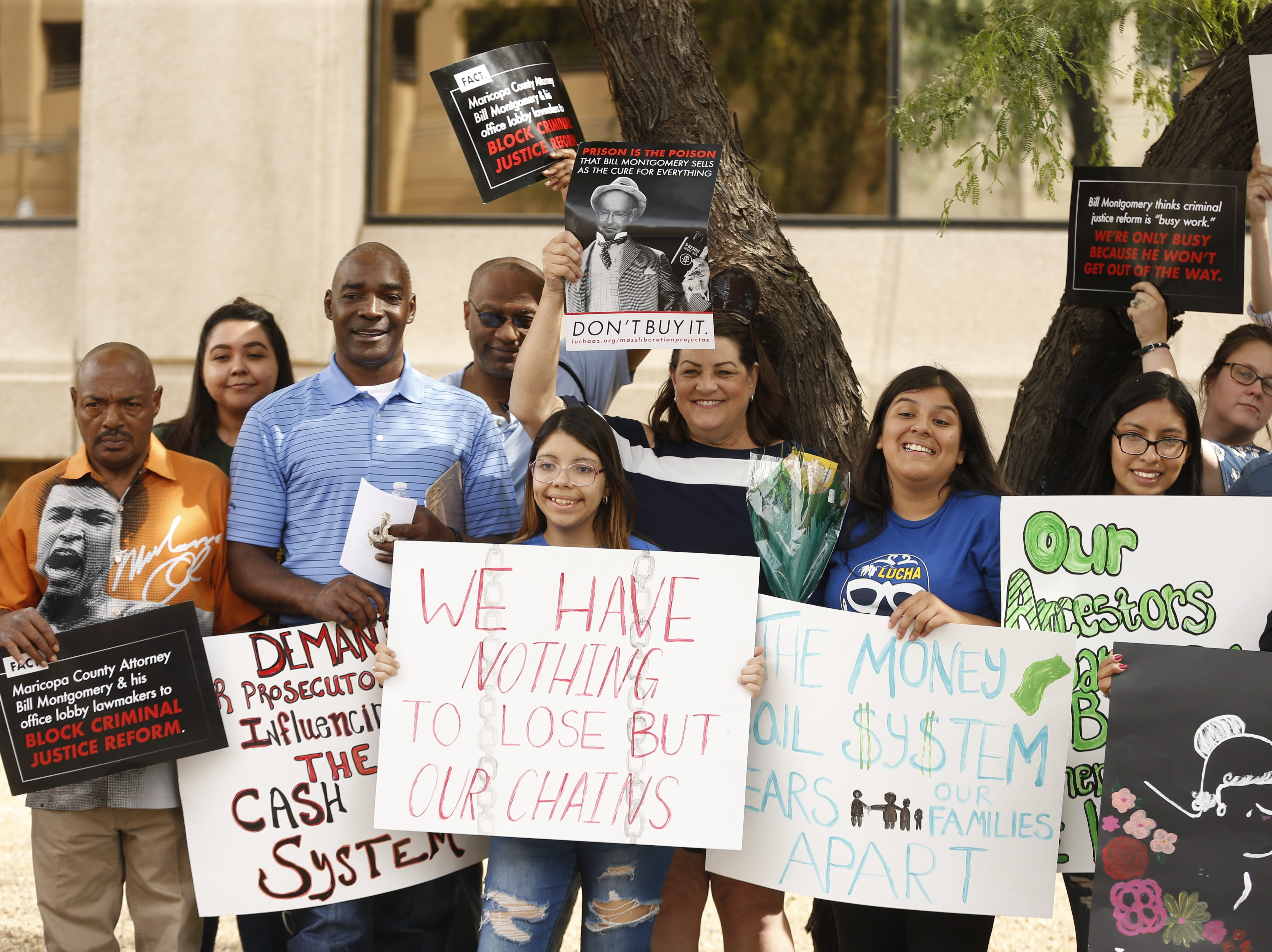 LUCHA members hold signs during a protest against cash bail at the Maricopa County Attorney's office in Phoenix on May 9, 2019.