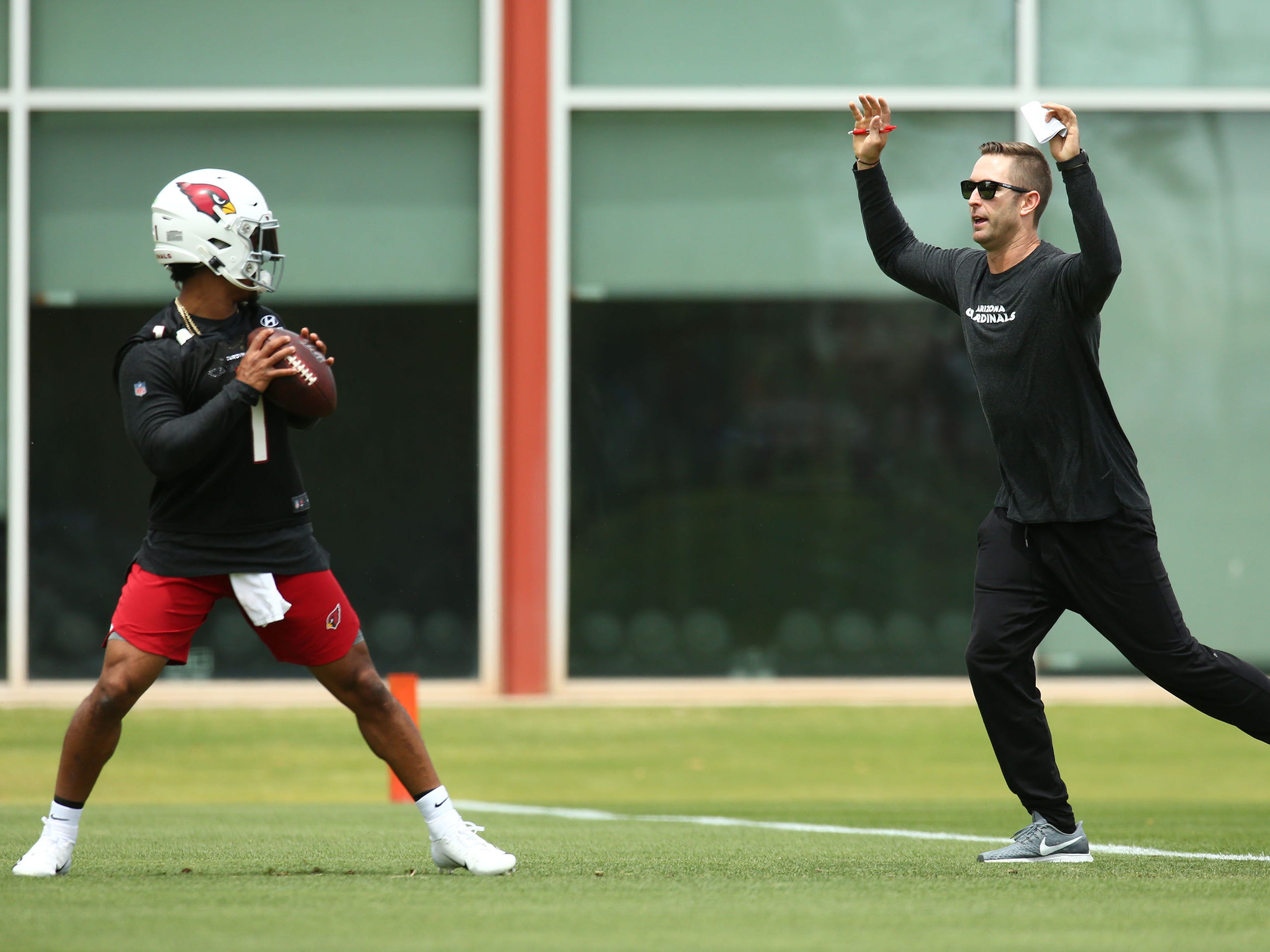 Cardinals quarterback Kyler Murray looks to throw over head coach Kliff Kingsbury during a drill on the first day of rookie minicamp.